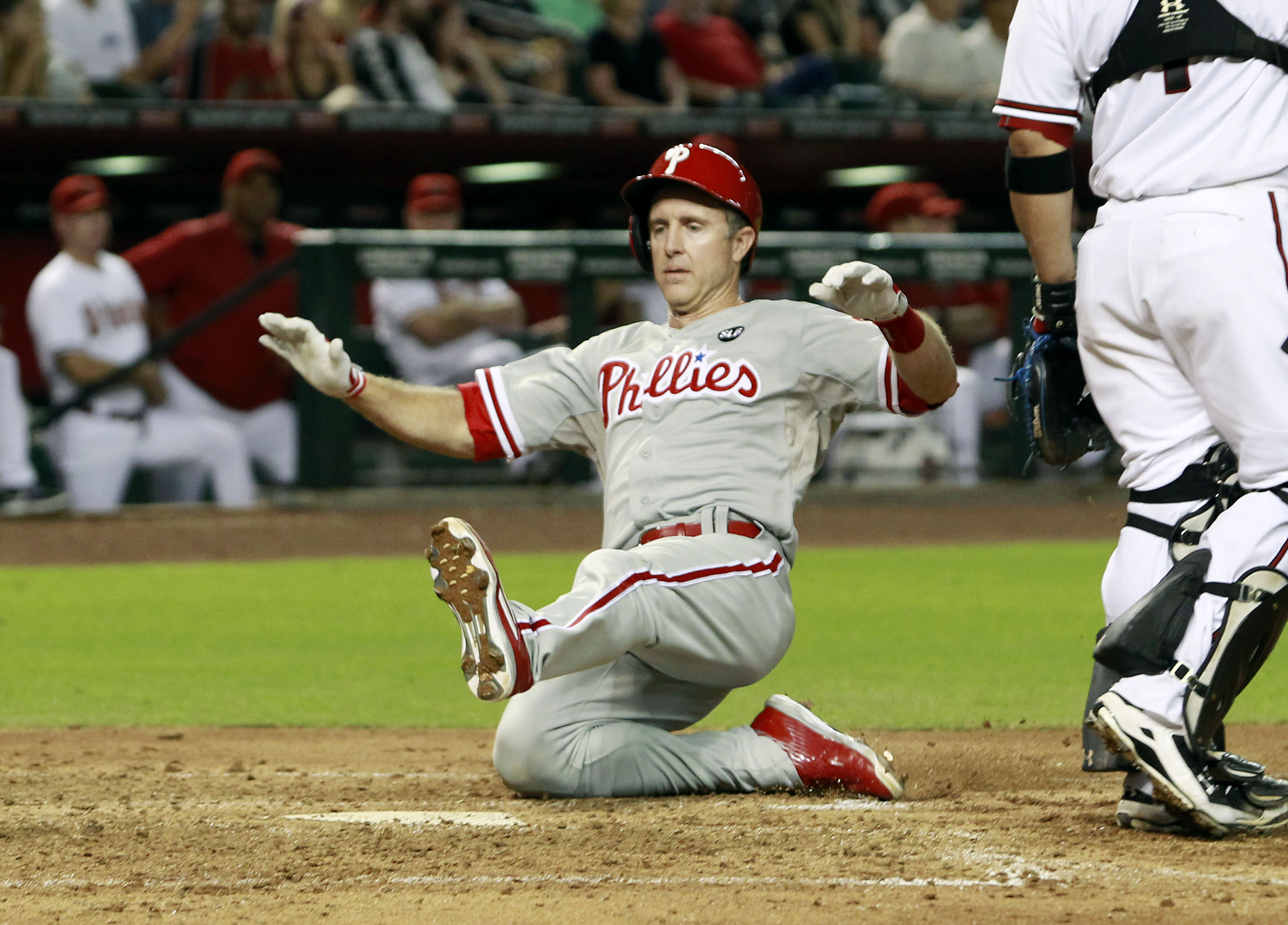 Philadelphia Phillies' Chase Utley, left, slides home to score a run against Arizona Diamondbacks on an RBI double by teammate Cesar Hernandez during the fifth inning of a baseball game, Monday, Aug. 10, 2015, in Phoenix. (AP Photo/Ralph Freso)