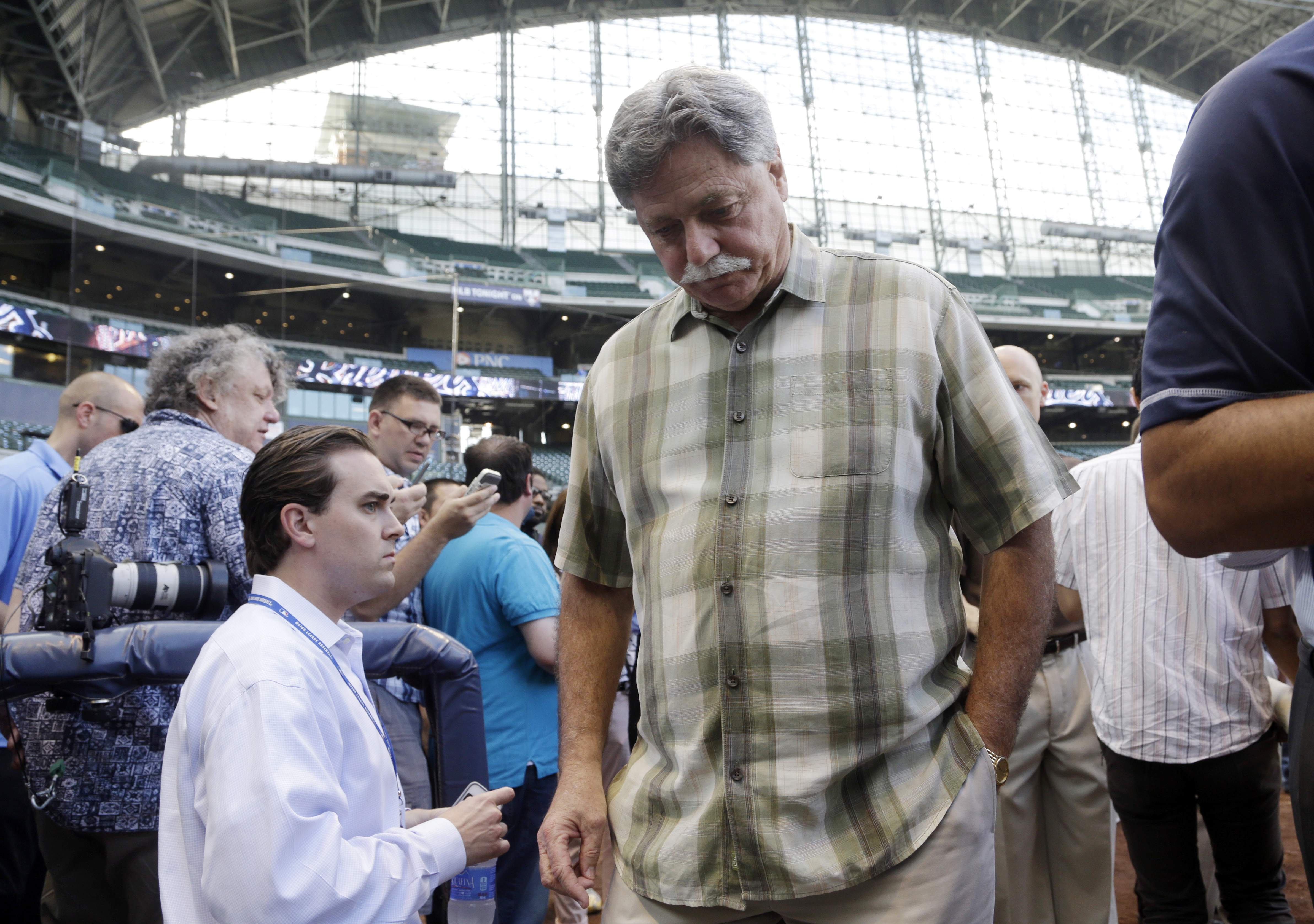 Milwaukee Brewers general manager Doug Melvin walks back to the clubhouse after talking to reporters about Ryan Braun's MLB suspension before a game against the San Diego Padres Monday, July 22, 2013, in Milwaukee. Braun, a former National League MVP , ha