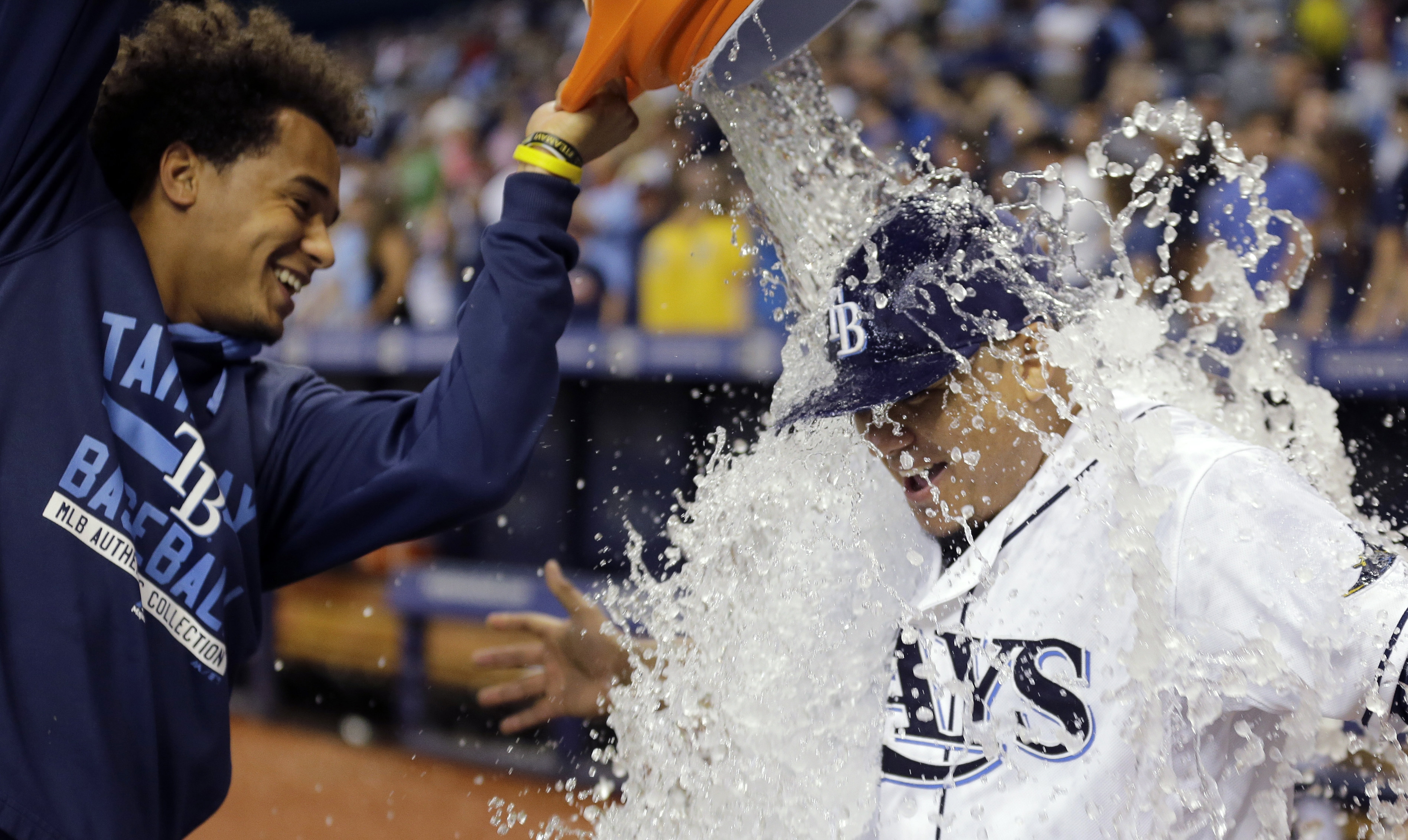 Tampa Bay Rays starting pitcher Erasmo Ramirez, right, gets doused with water by teammate Chris Archer as Ramirez is interviewed following the team's 2-0 win over the Atlanta Braves during a baseball game Tuesday, Aug. 11, 2015, in St. Petersburg, Fla. (A