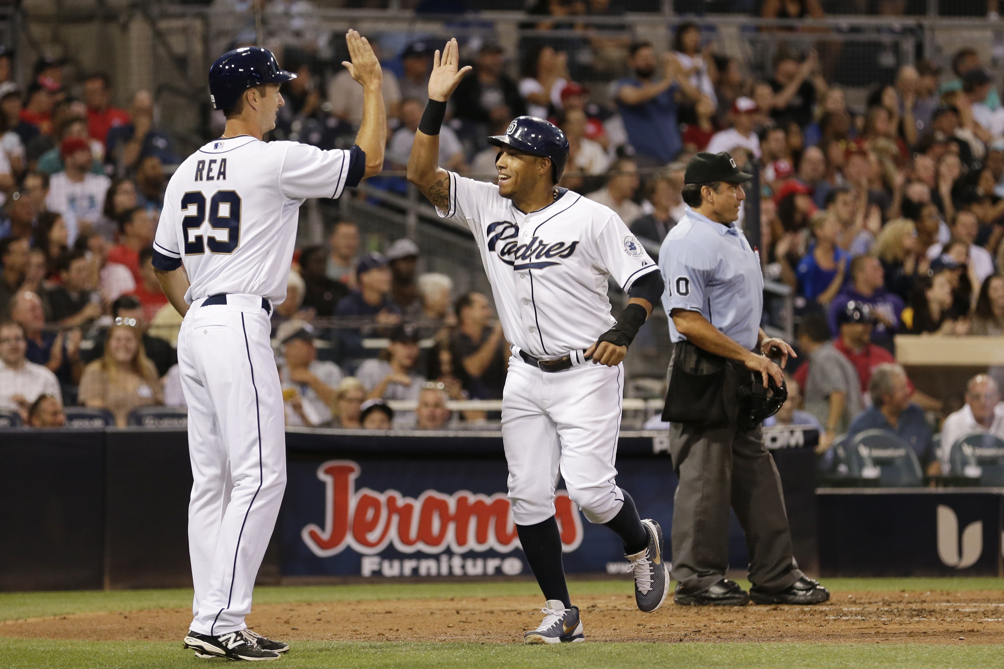 San Diego Padres' Yangervis Solarte, right, and teammate Colin Rea celebrate after scoring off a two-run double by Yonder Alonso against the Cincinnati Reds during the second inning of a baseball game, Tuesday, Aug. 11, 2015, in San Diego. (AP Photo/Grego