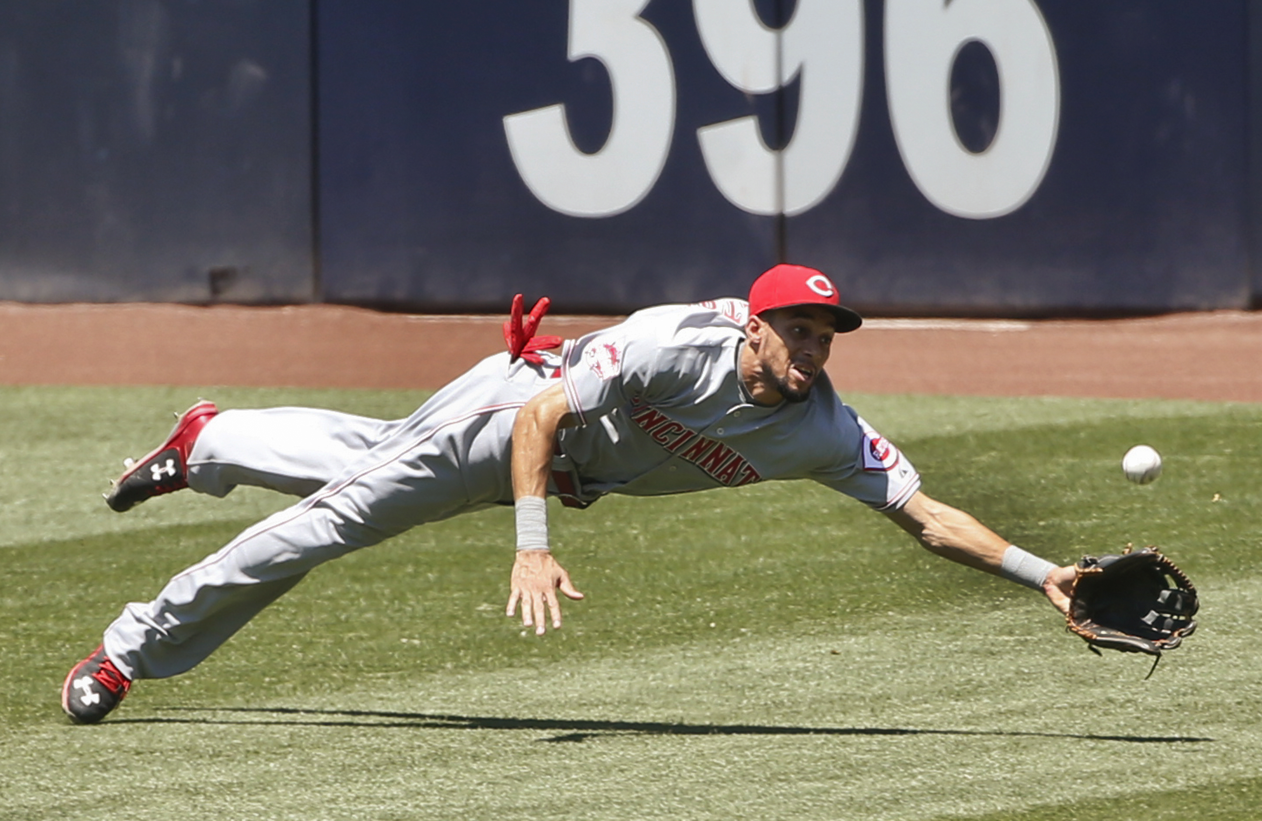 Cincinnati Reds center fielder Billy Hamilton misses on a diving attempt at a drive hit by San Diego Padres' Derek Norris during the first inning of a baseball game Wednesday, Aug. 12, 2015, in San Diego. Norris doubled on the play. (AP Photo/Lenny Ignelz