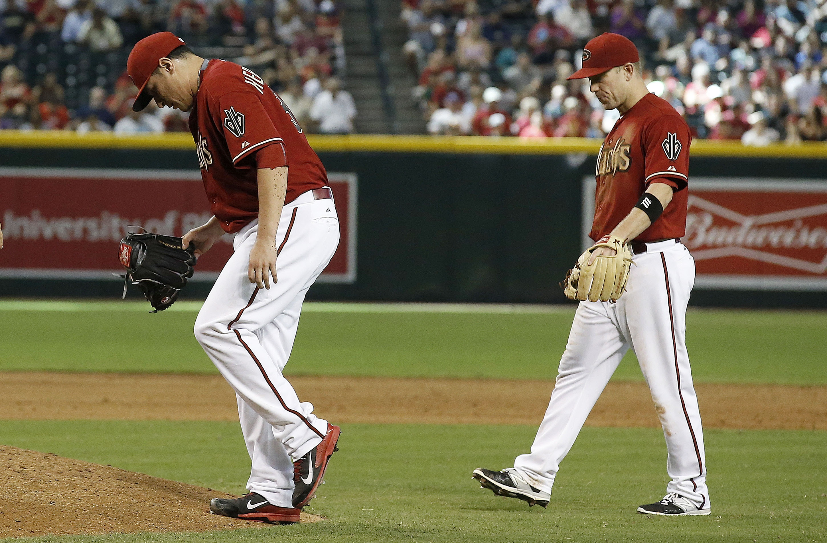 Arizona Diamondbacks' Aaron Hill, right, walks in to check on pitcher David Hernandez, left, who was hit on the leg by a line drive by Philadelphia Phillies' Andres Blanco during the sixth inning of a baseball game Wednesday, Aug. 12, 2015, in Phoenix. He