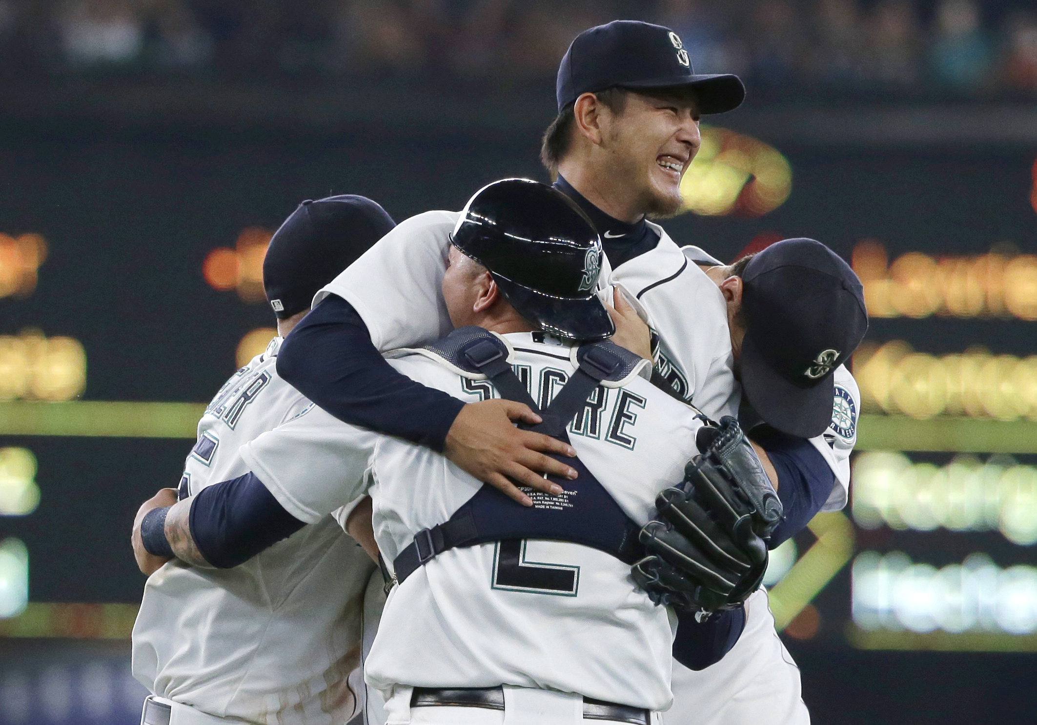 Seattle Mariners starting pitcher Hisashi Iwakuma, center, is mobbed by teammates, including catcher Jesus Sucre (2), after Iwakuma threw a no-hitter against the Baltimore Orioles in a baseball game Wednesday, Aug. 12, 2015, in Seattle. The Mariners won 3