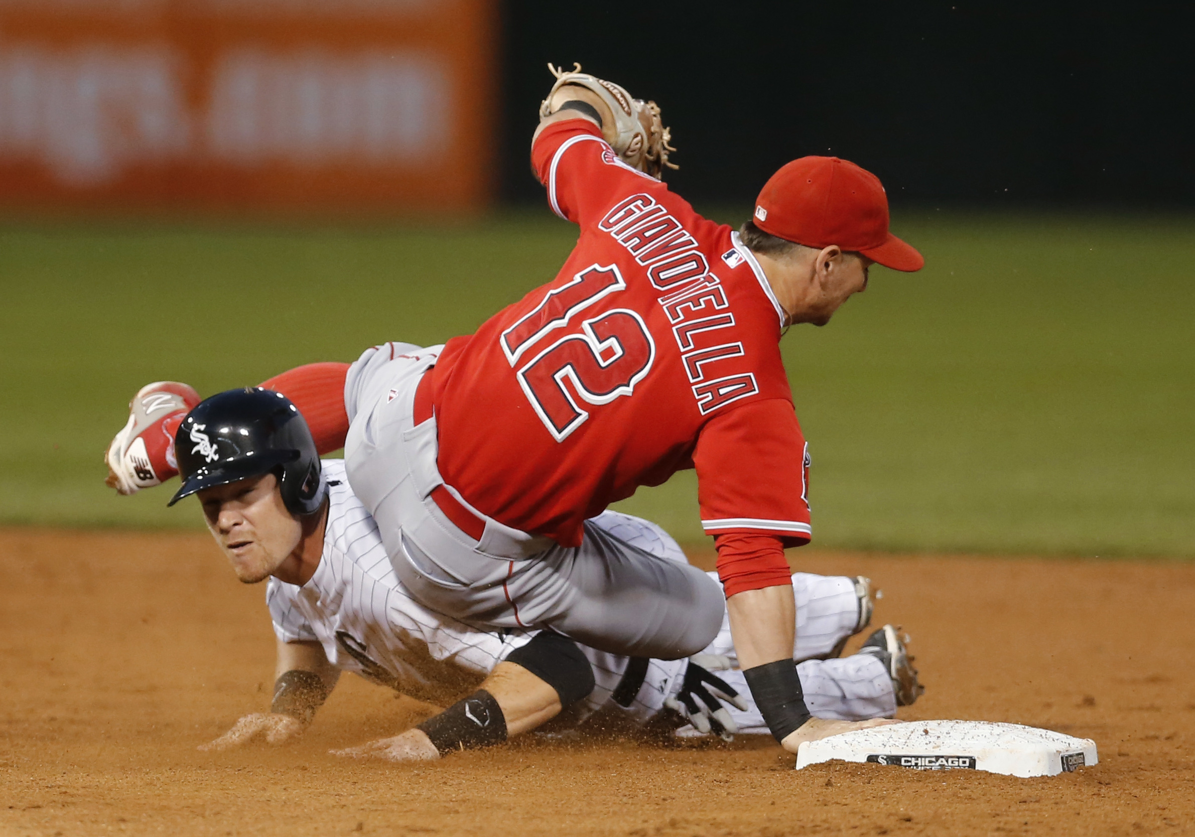 Los Angeles Angels second baseman Johnny Giavotella (12) tumbles over Chicago White Sox's Gordon Beckham after throwing to first to complete a double play on Tyler Saladino during the third inning of a baseball game Wednesday, Aug. 12, 2015, in Chicago. (