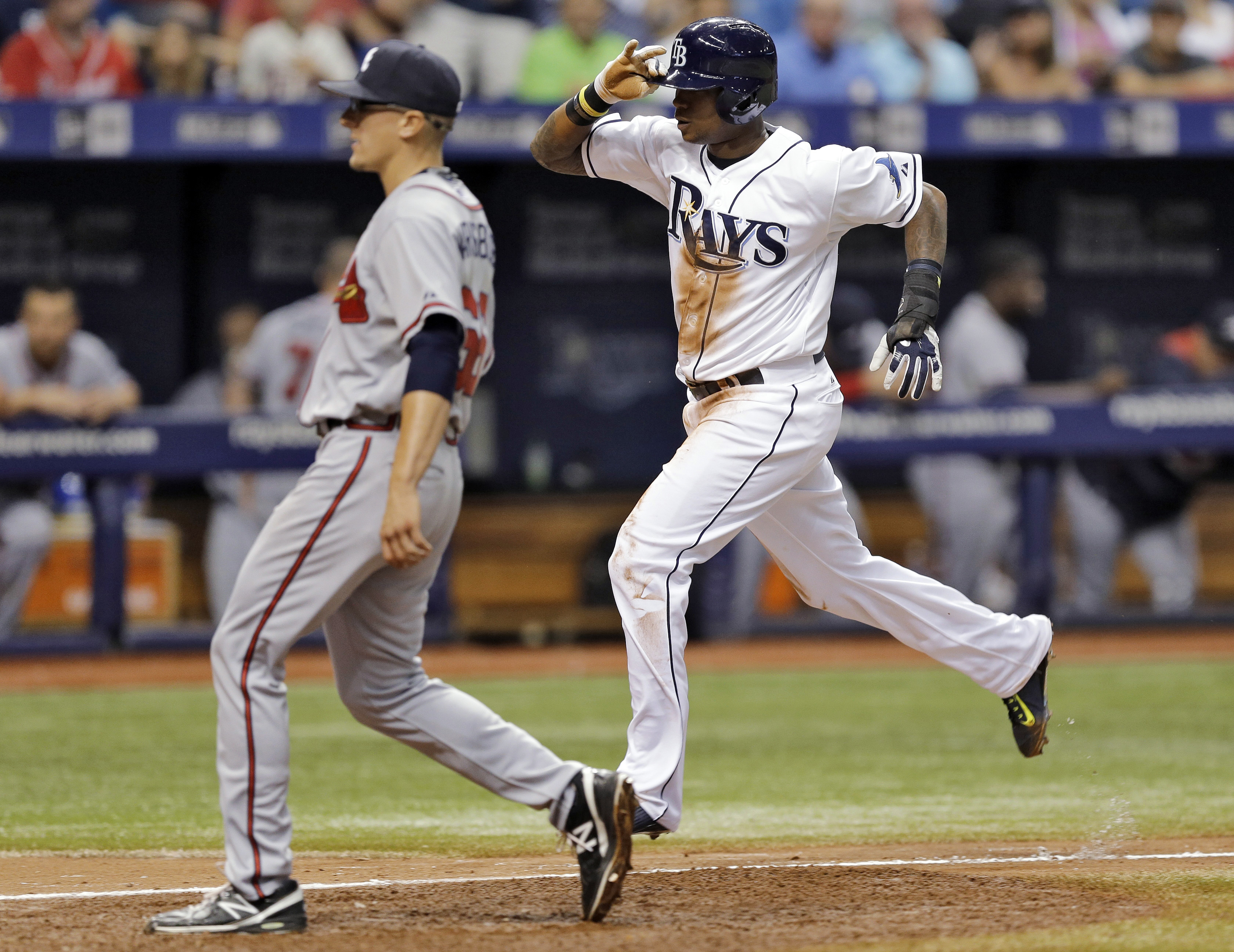 Tampa Bay Rays' Tim Beckham, right, scores next to Atlanta Braves relief pitcher Matt Marksberry on a wild pitch by Marksberry during the seventh inning of a baseball game Wednesday, Aug. 12, 2015, in St. Petersburg, Fla. (AP Photo/Chris O'Meara)