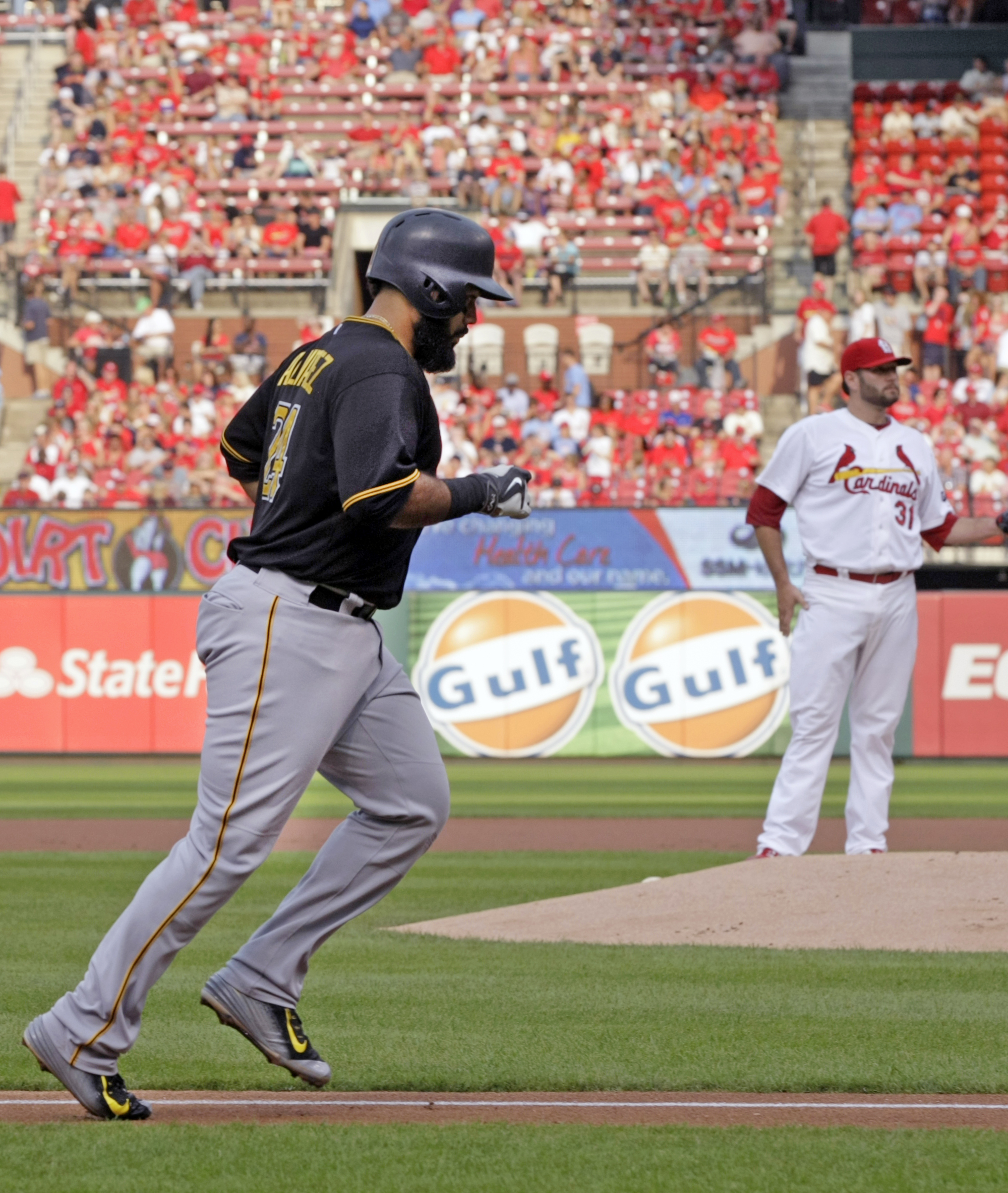 Pittsburgh Pirates' Pedro Alvarez, left, circles the bases as St. Louis Cardinals starting pitcher Lance Lynn looks on, after Alvarez hit a two-run home run in the first inning of a baseball game, Thursday, Aug. 13, 2015, in St. Louis. (AP Photo/Tom Ganna