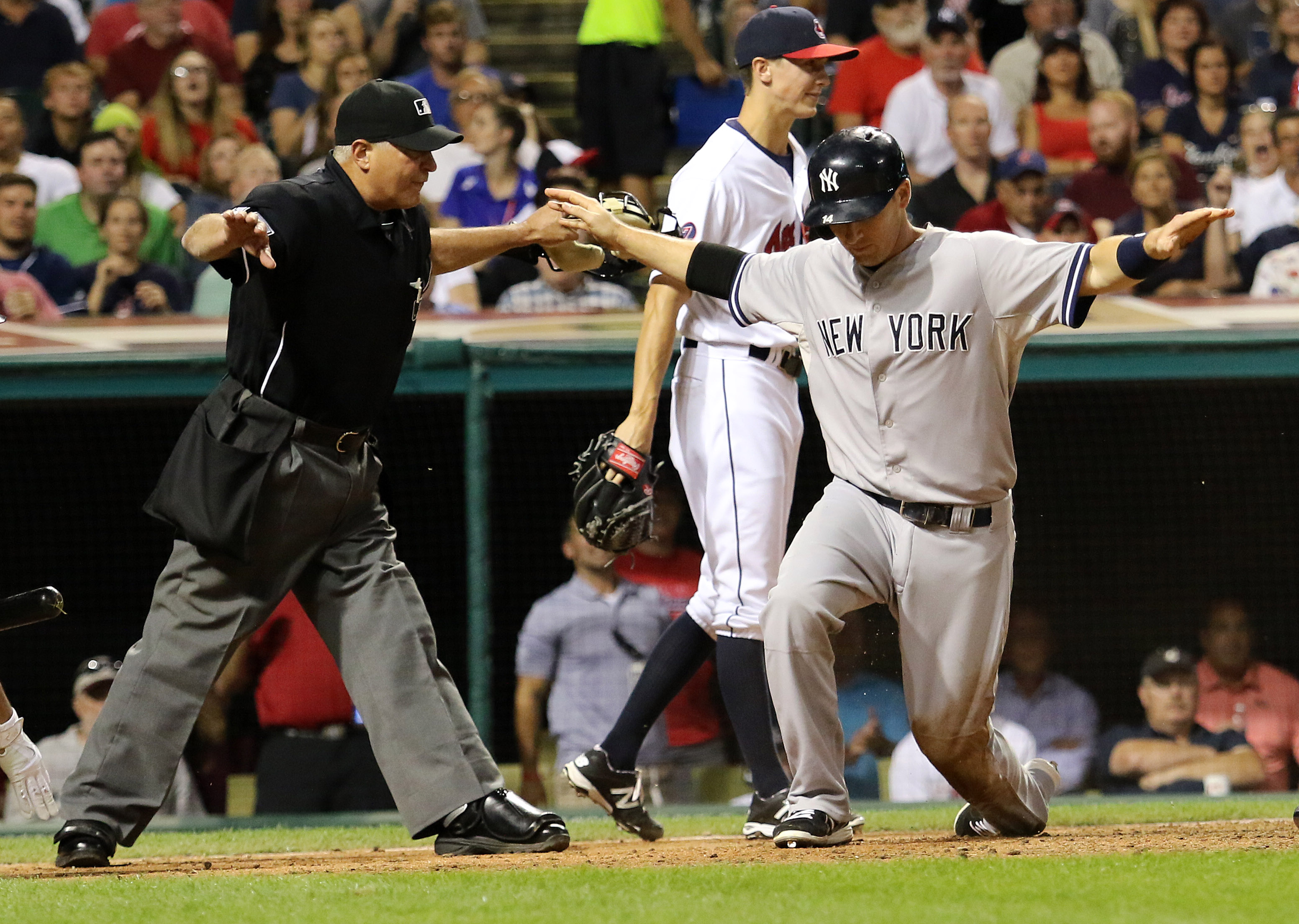 New York Yankees Stephen Drew, right, and  umpire John Hirschbeck both signal that Drew is safe, after he scored on a single by Brad Gardner duirng the sixth inning of a baseball game against the Cleveland Indians on Thursday, Aug. 13, 2015, in Cleveland.