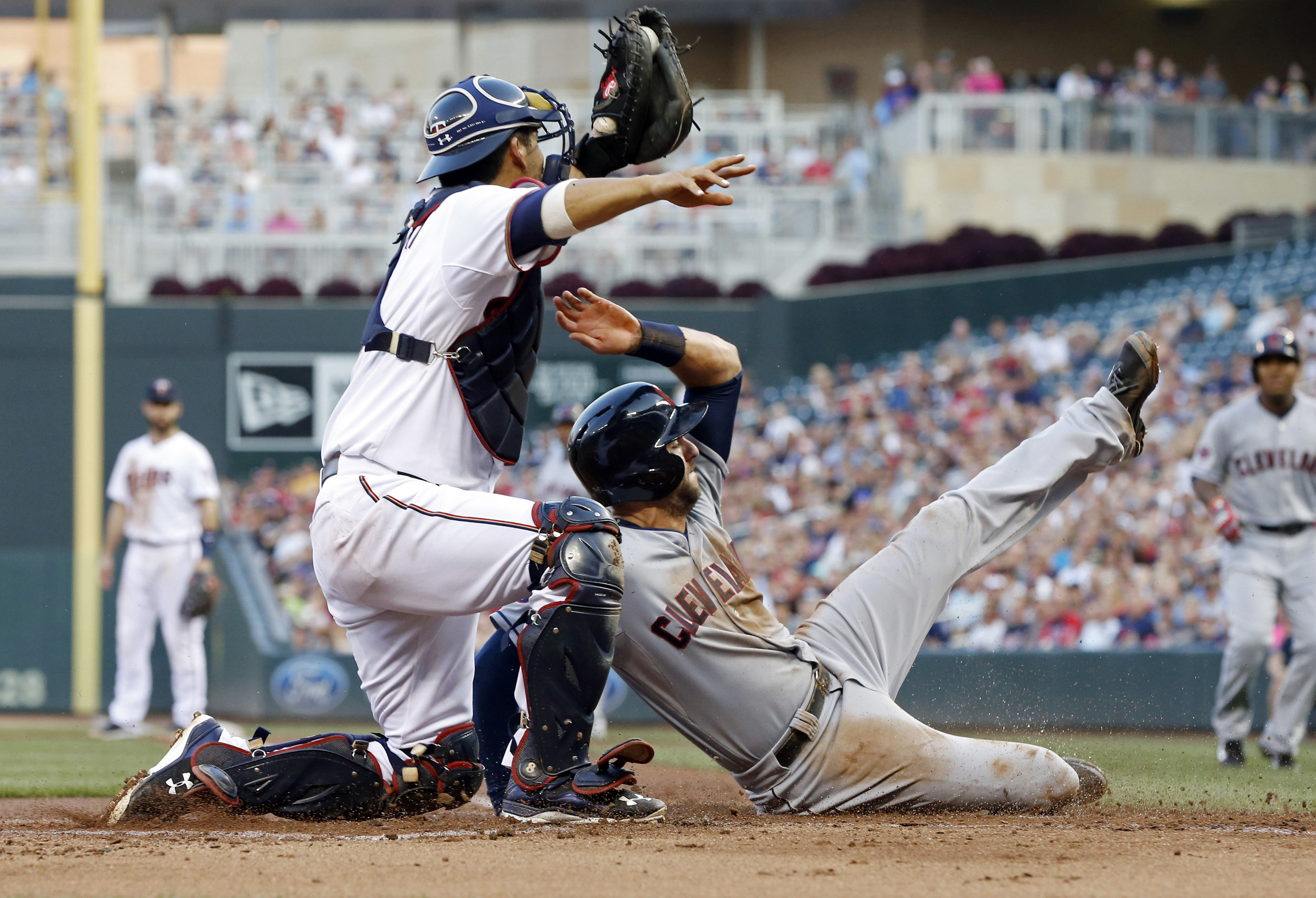 Cleveland Indians' Lonnie Chisenhall, right, is tagged out by Minnesota Twins catcher Kurt Suzuki as he tried to score on a hit by Mike Aviles in the second inning of a baseball game, Friday, Aug. 14, 2015, in Minneapolis. Chisenhall was originally called