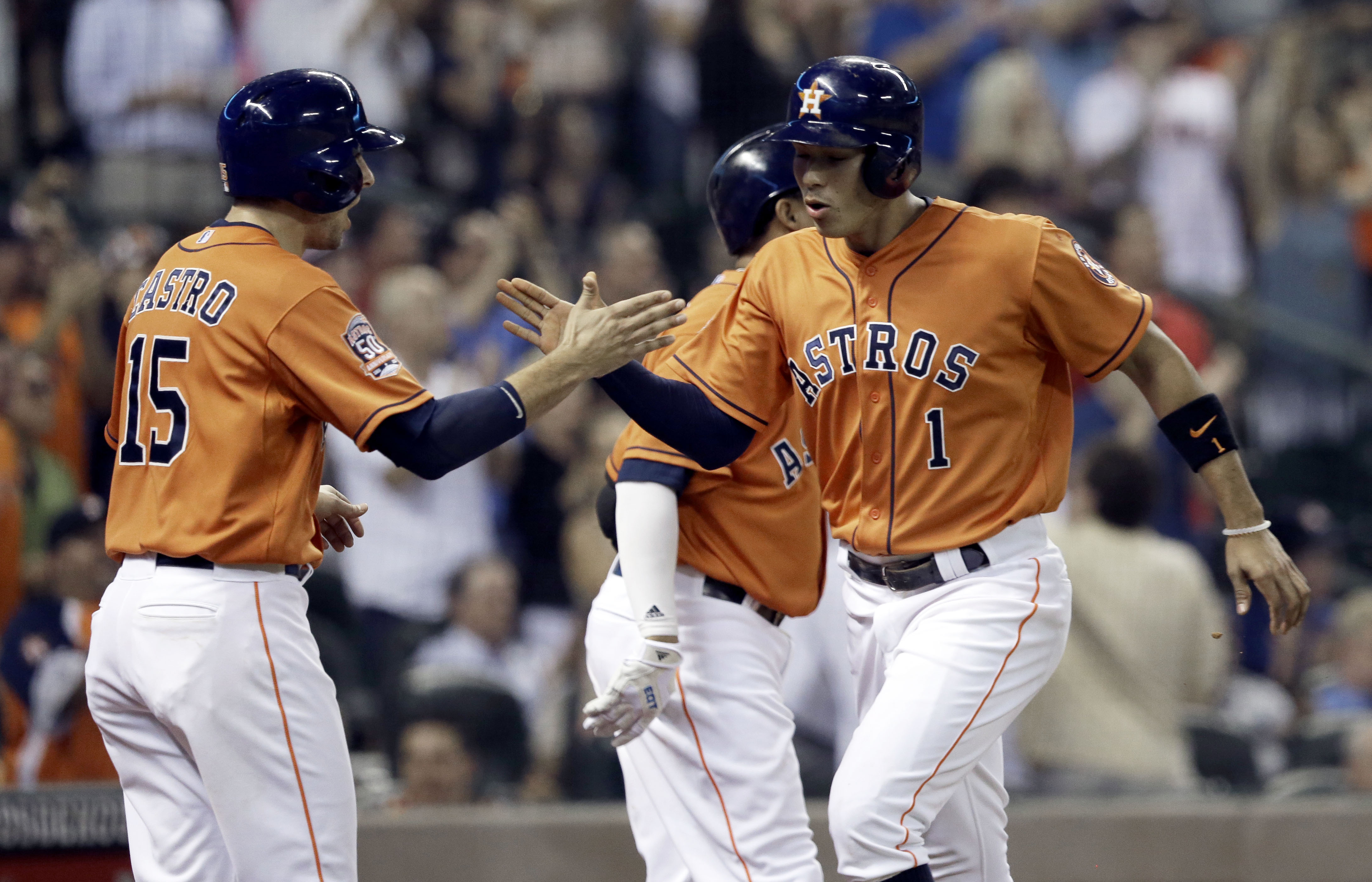 Houston Astros' Jason Castro (15) and Carlos Correa (1) celebrate scoring on a double by Jed Lowrie against the Detroit Tigers during the fifth inning of a baseball game Friday, Aug. 14, 2015, in Houston. (AP Photo/Pat Sullivan)
