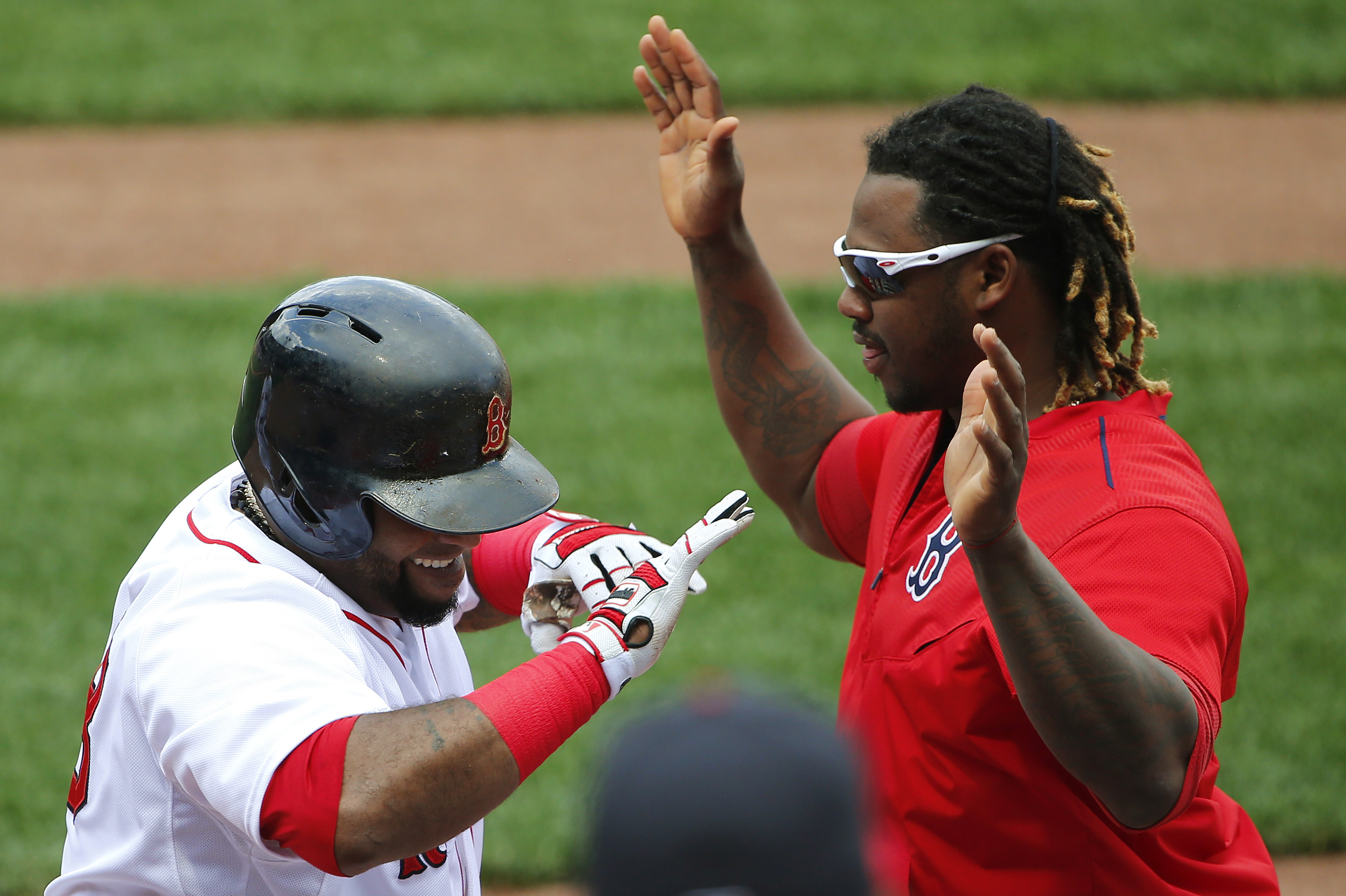 Boston Red Sox's Pablo Sandoval is greeted at the dugout by teammate Hanley Ramirez after his home run against the Seattle Mariners during the second inning of a baseball game at Fenway Park in Boston Saturday, Aug. 15, 2015.  (AP Photo/Winslow Townson)