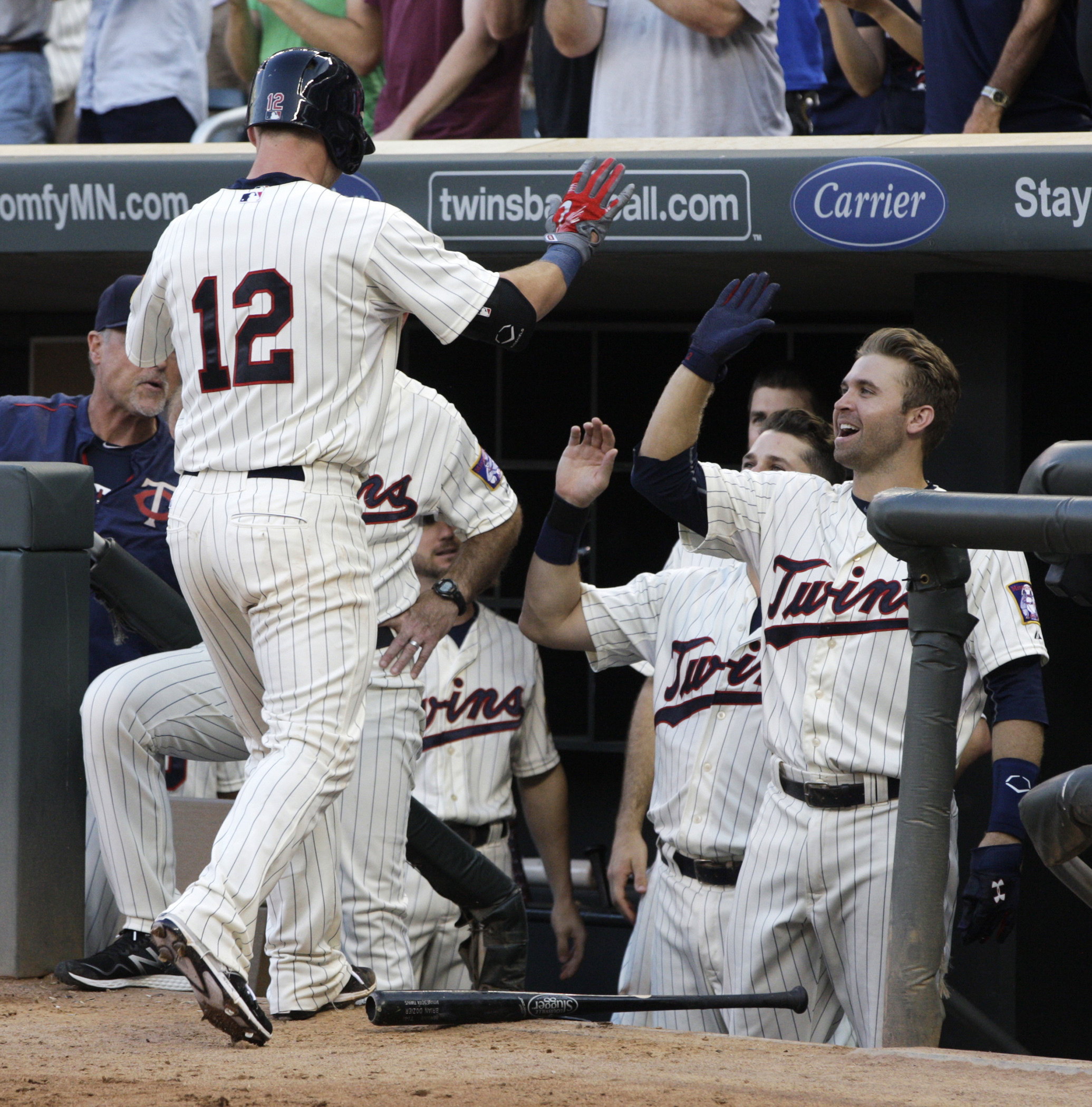 Minnesota Twins' Chris Herrmann (12) is congratulated by teammate Brian Dozier, right, after hitting a solo home run off Cleveland Indians starting pitcher Josh Tomlin during the fifth inning of a baseball game Saturday, Aug. 15, 2015, in Minneapolis. AP