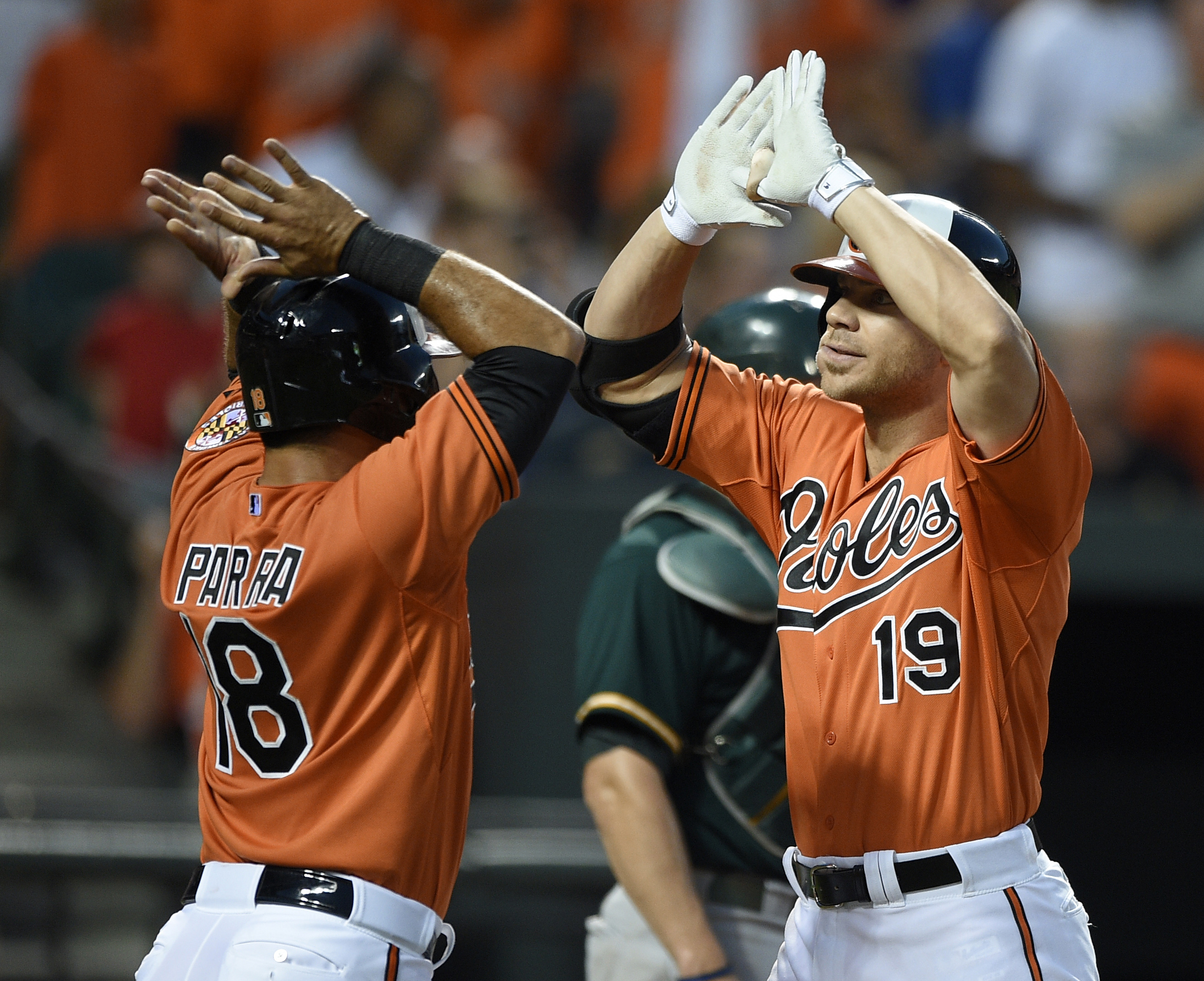 Baltimore Orioles' Chris Davis (19) celebrates his two-run home run with Gerardo Parra (18) against the Oakland Athletics during the fourth inning of a baseball game, Saturday, Aug. 15, 2015, in Baltimore. (AP Photo/Nick Wass)