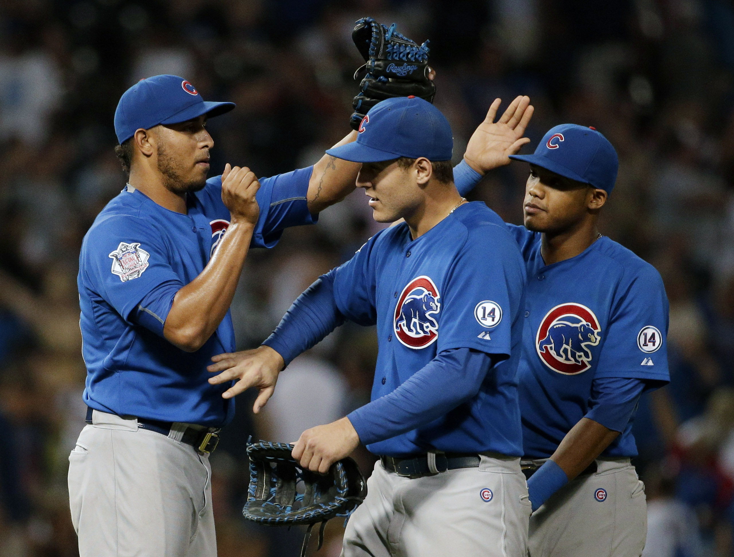 Chicago Cubs closer Hector Rondon, left, celebrates with Anthony Rizzo, center, and Addison Russell after the Chicago Cubs defeated the Chicago White Sox 6-3 in an interleague baseball game Saturday, Aug. 15, 2015,  in Chicago. (AP Photo/Nam Y. Huh)