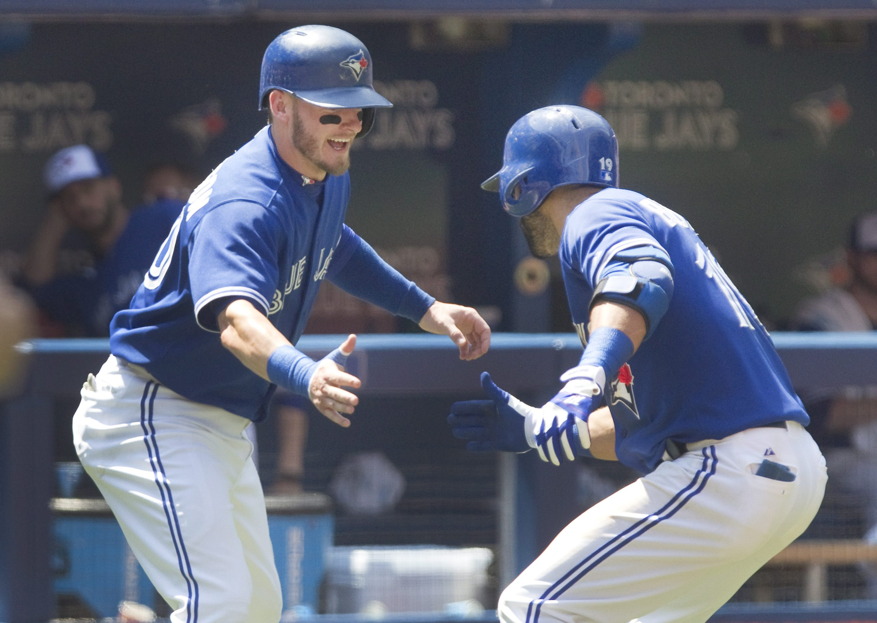 Toronto Blue Jays' Jose Bautista, right, is met by teammate Josh Donaldson after hitting two-run home run against the New York Yankees in the third inning of a baseball game in Toronto, Sunday, Aug. 16, 2015. (Fred Thornhill/The Canadian Press via AP) MAN