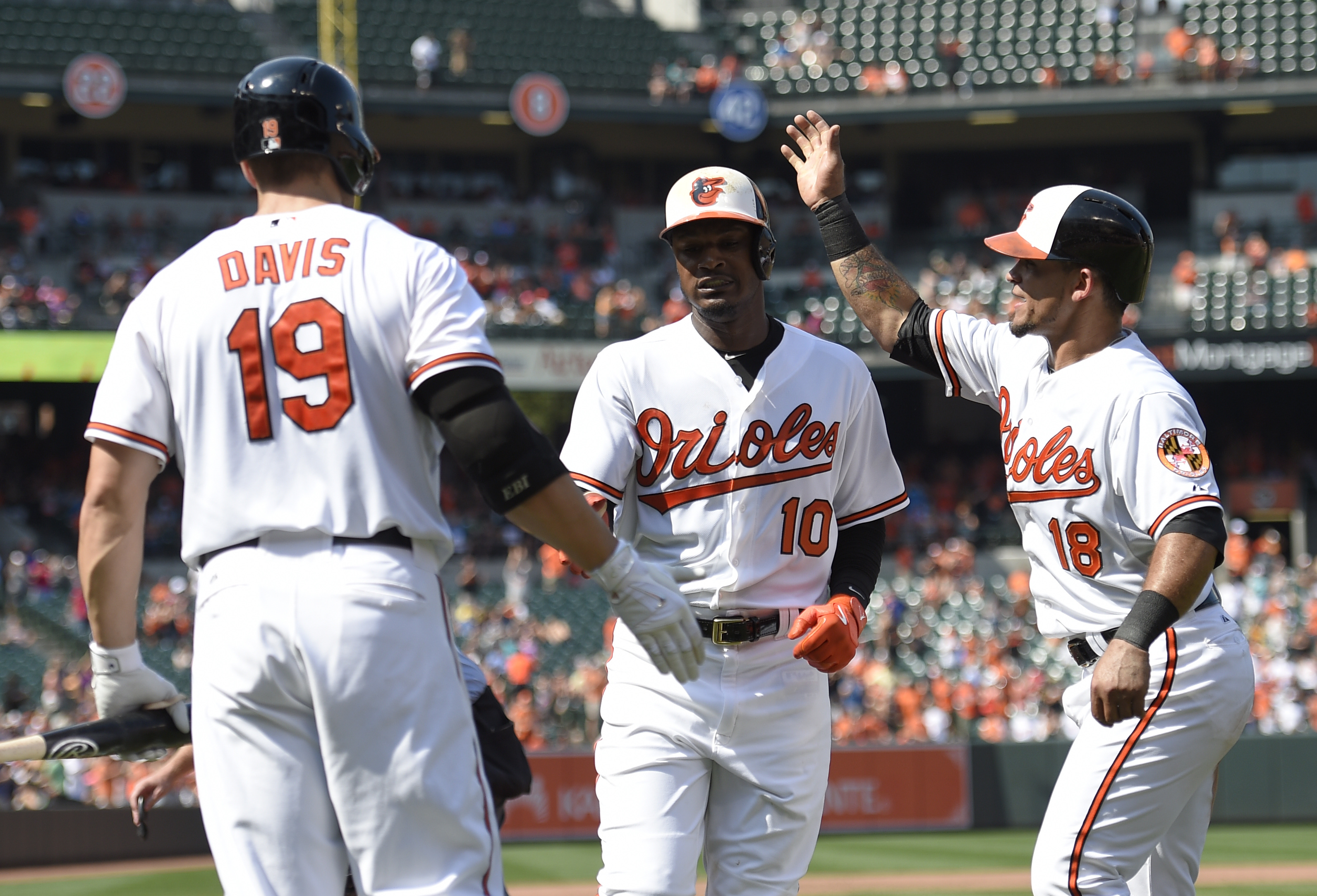 Baltimore Orioles' Adam Jones (10) celebrates his two-run home run with teammates Gerardo Parra (18) and Chris Davis (19) during the fifth inning of a baseball game against the Oakland Athletics, Sunday, Aug. 16, 2015, in Baltimore. (AP Photo/Nick Wass)