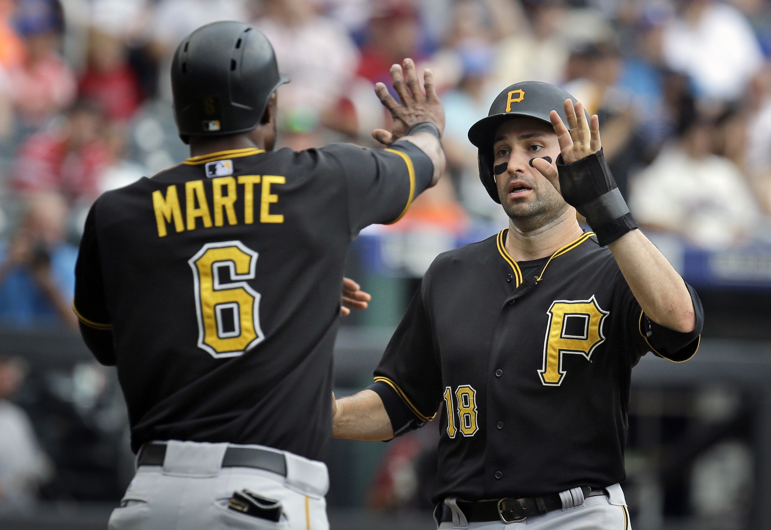 Pittsburgh Pirates' Neil Walker, right, and Starling Marte celebrate after scoring on a double hit by Aramis Ramirez during the eighth inning of the baseball game against the New York Mets at Citi Field, Sunday, Aug. 16, 2015, in New York. (AP Photo/Seth