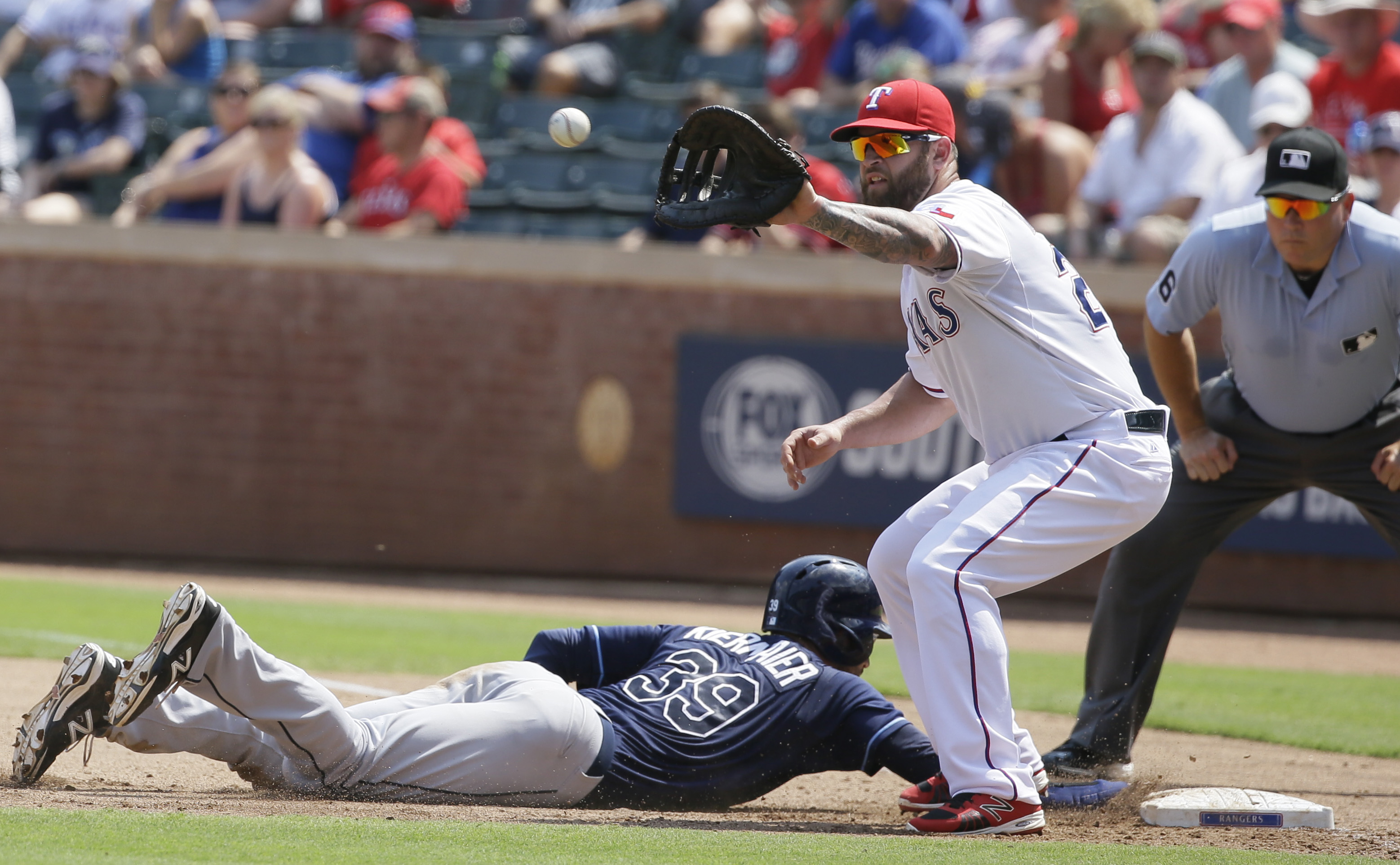 Tampa Bay Rays Kevin Kiermaier dives back to base as Texas Rangers first baseman Mike Napoli (25) waits for the pick-off throw during the fourth inning of a baseball game in Arlington, Texas, Sunday, Aug. 16, 2015. (AP Photo/LM Otero)