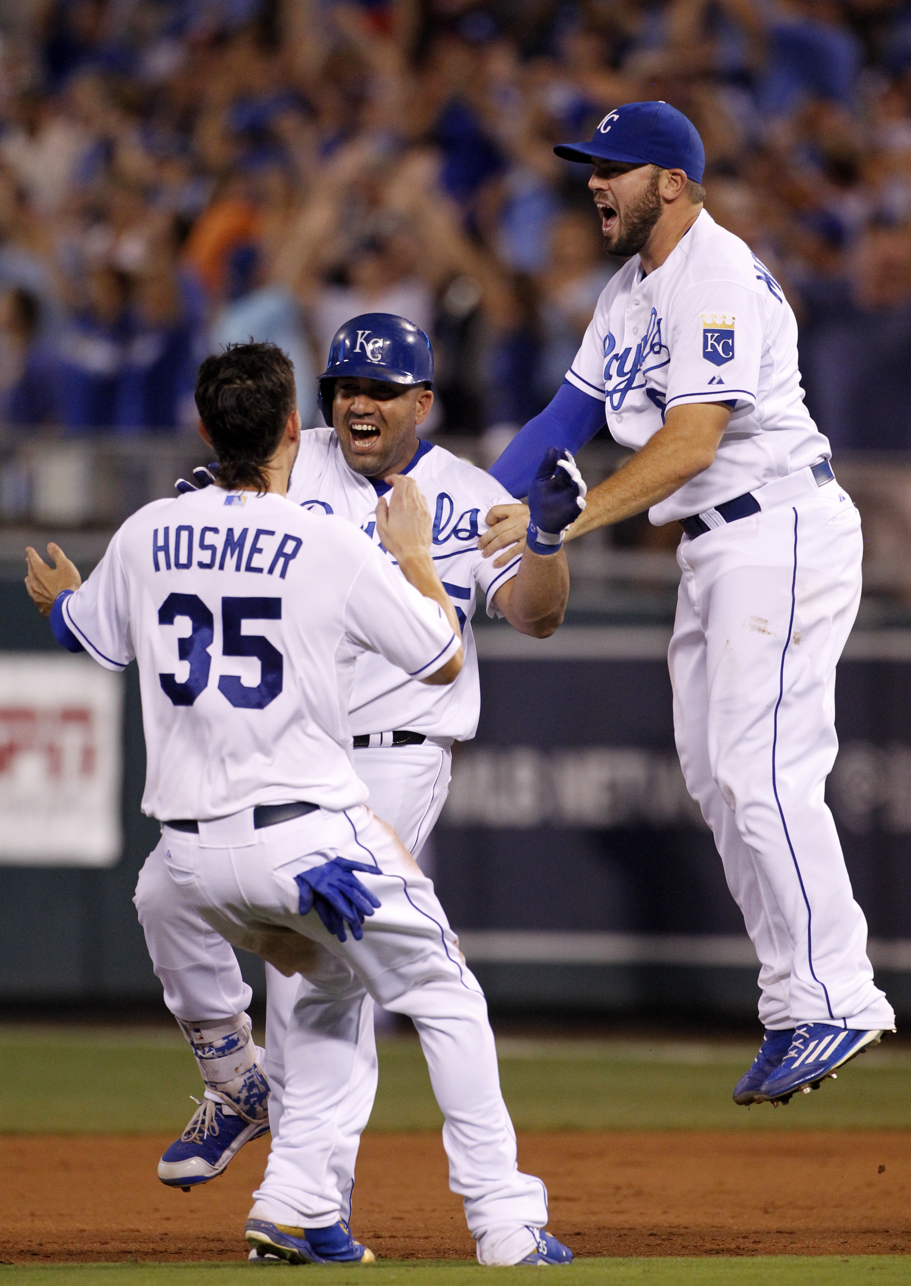 Kansas City Royals designated hitter Kendrys Morales, center, celebrates his game-winning hit with Eric Hosmer, left, and Mike Moustakas, right, in the 10th inning of a baseball game against the Los Angeles Angels at Kauffman Stadium in Kansas City, Mo.,