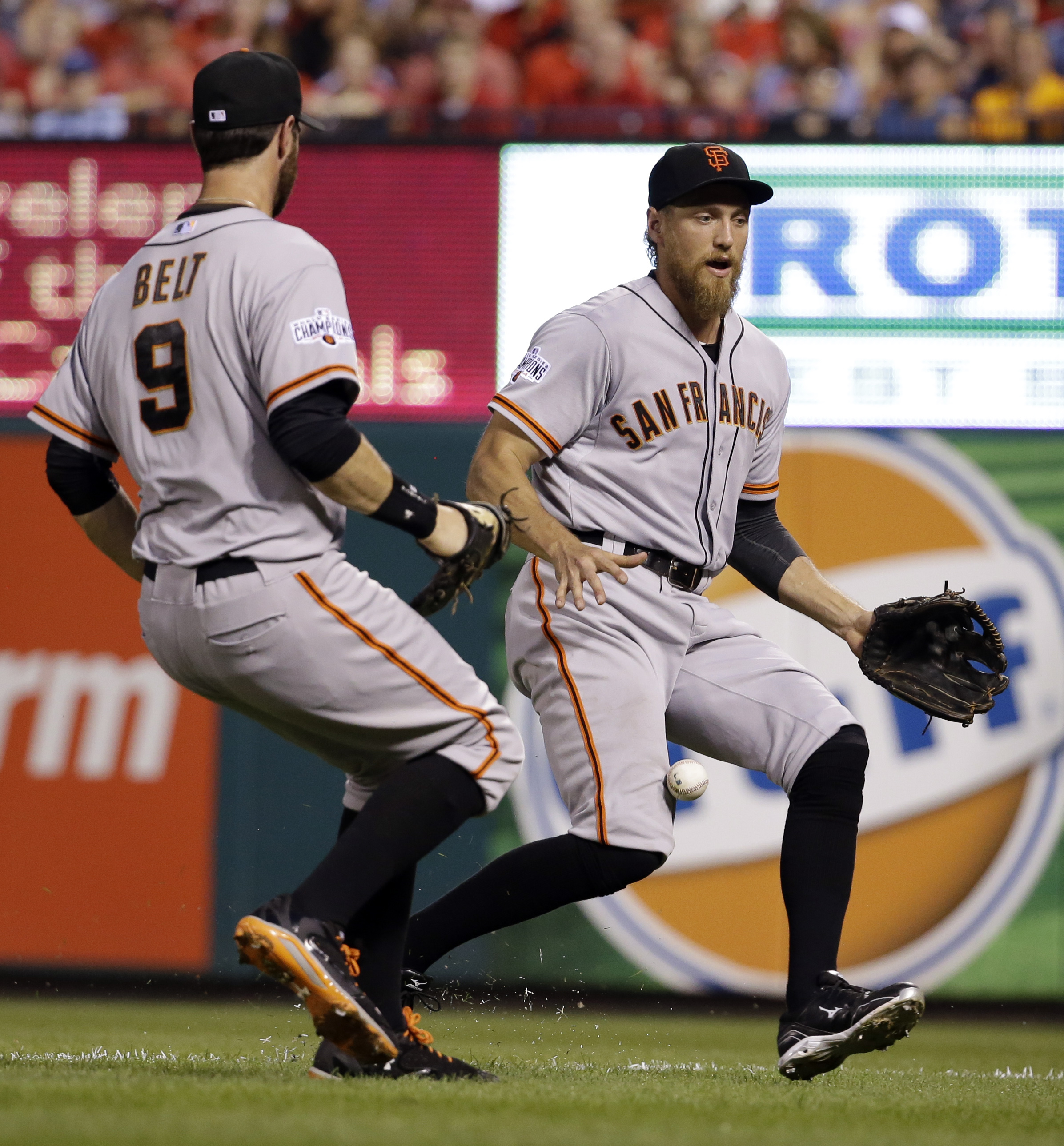 San Francisco Giants right fielder Hunter Pence, right, and first baseman Brandon Belt can't reach a foul ball hit by St. Louis Cardinals' Michael Wacha during the third inning of a baseball game Monday, Aug. 17, 2015, in St. Louis. (AP Photo/Jeff Roberso