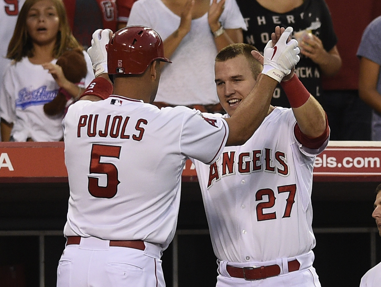 Los Angeles Angels' Albert Pujols, left, celebrates with Mike Trout, right, after hitting a solo home run during the second inning of a baseball game in Anaheim, Calif., Monday, Aug. 17, 2015. (AP Photo/Kelvin Kuo)