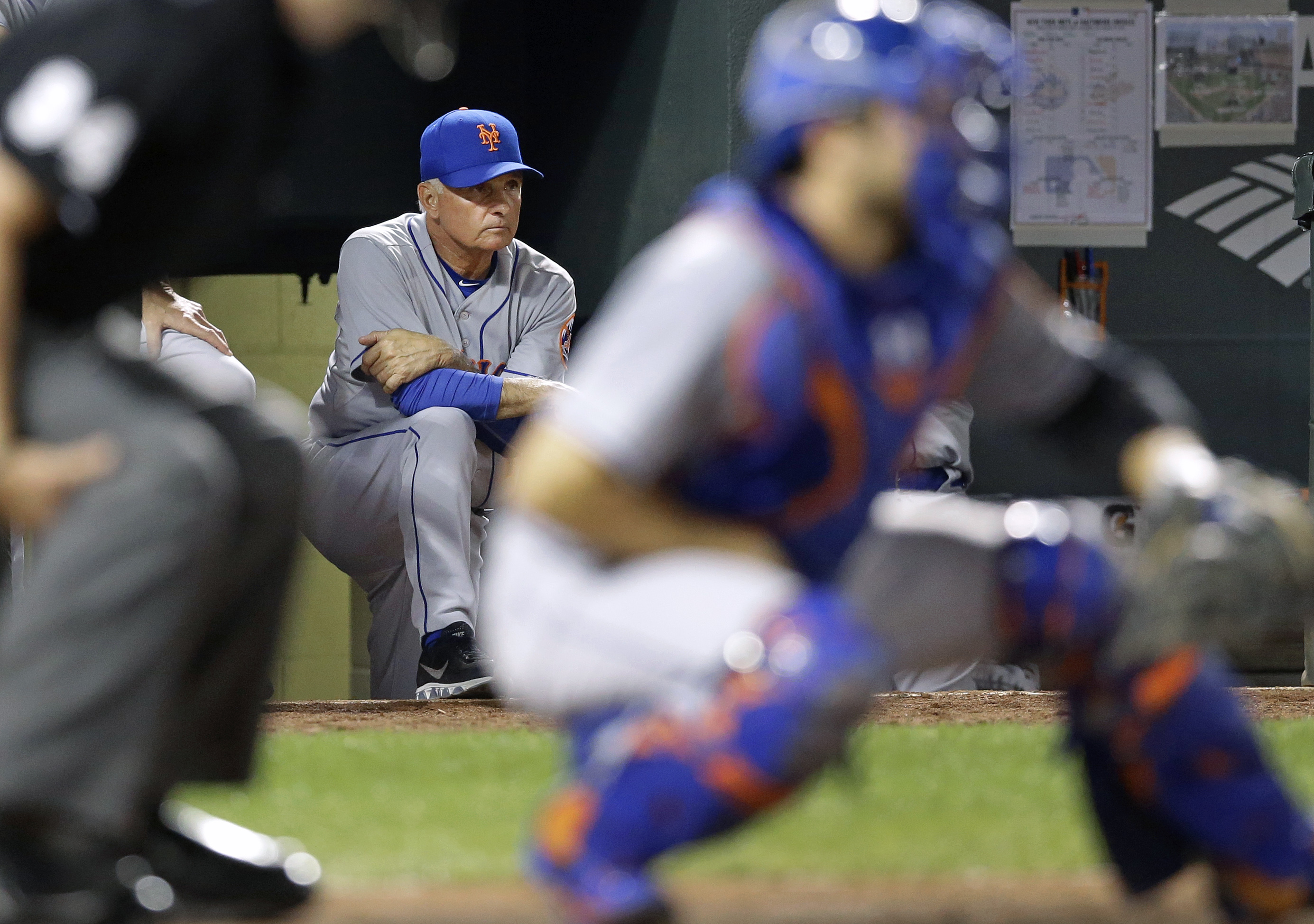 New York Mets manager Terry Collins, back, watches from the dugout in the fourth inning of a baseball game against the Baltimore Orioles, Tuesday, Aug. 18, 2015, in Baltimore. (AP Photo/Patrick Semansky)