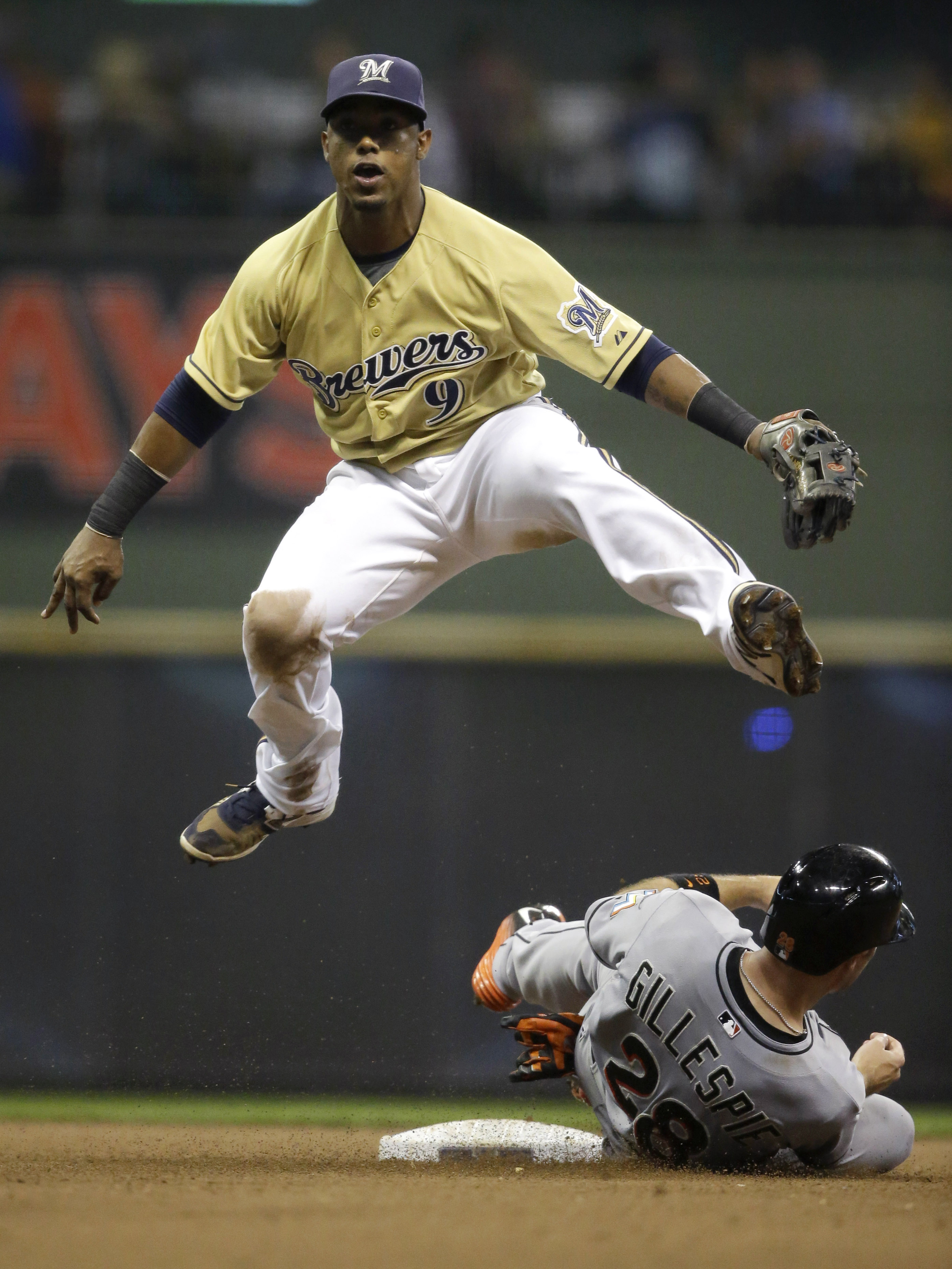 Milwaukee Brewers' Jean Segura (9) forces out Miami Marlins' Cole Gillespie at second base and completes the double play on the Marlins' Adeiny Hechavarria during the sixth inning of a baseball game Tuesday, Aug. 18, 2015, in Milwaukee. (AP Photo/Jeffrey