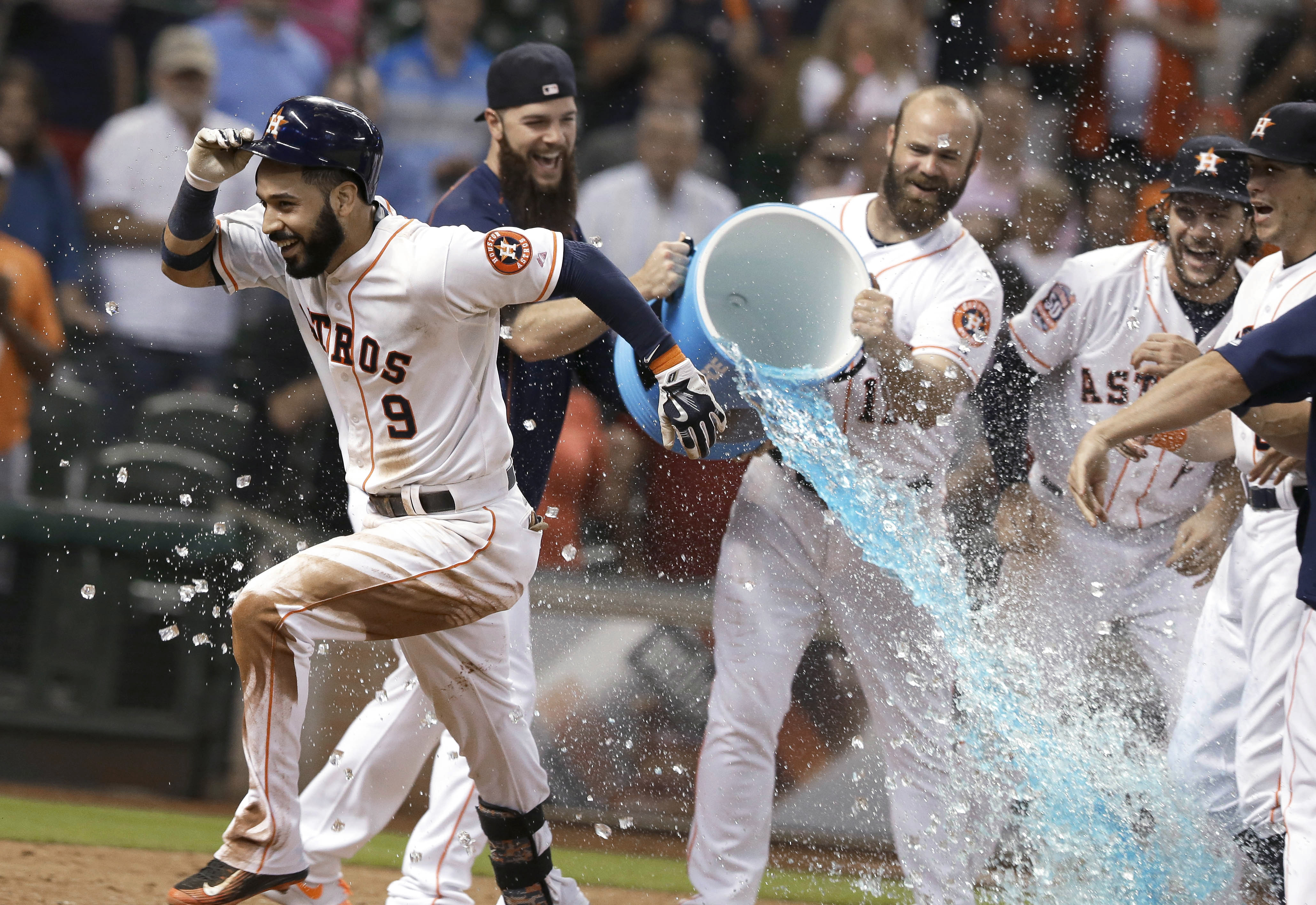 Houston Astros' Marwin Gonzalez (9) runs through a gauntlet of teammates, some trying to douse him, after hitting a walk-off home run in the 10th inning of a baseball game against the Tampa Bay Rays on Tuesday, Aug. 18, 2015, in Houston. The Astros won 3-
