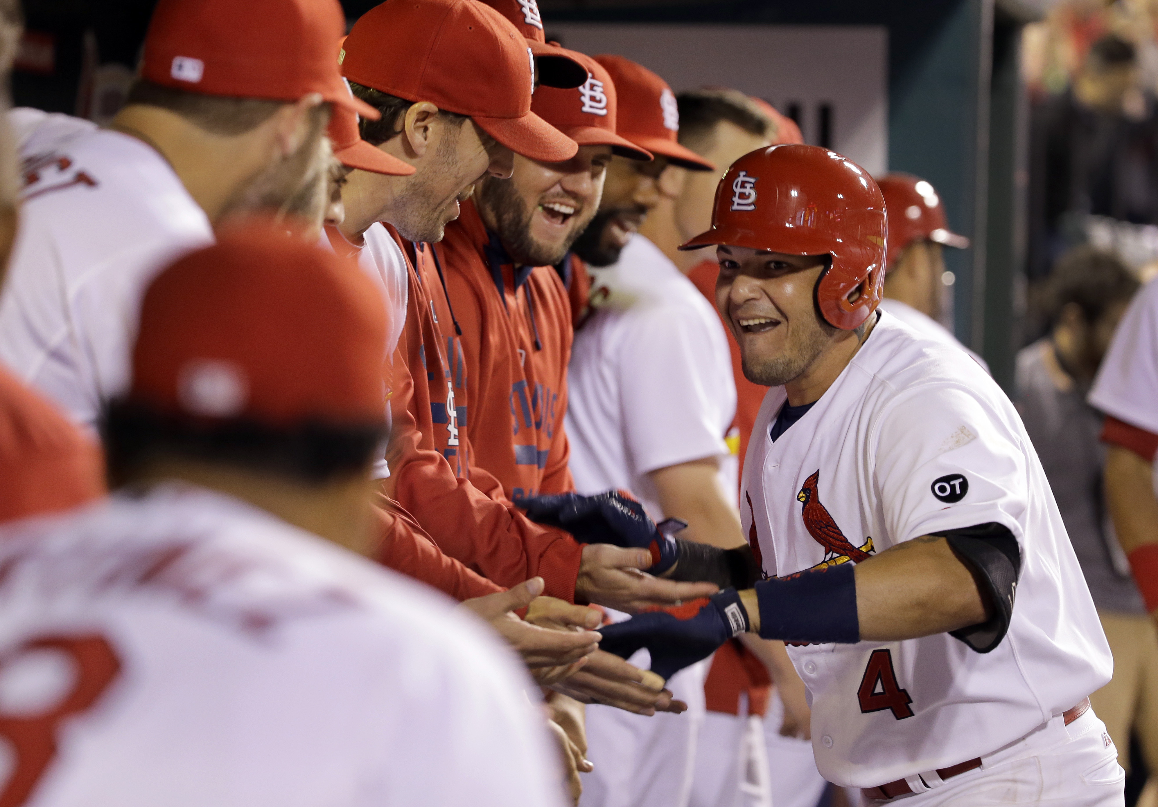 St. Louis Cardinals' Yadier Molina, right, is congratulated by teammates in the dugout after hitting a solo home run during the eighth inning of a baseball game against the San Francisco Giants, Wednesday, Aug. 19, 2015, in St. Louis. (AP Photo/Jeff Rober