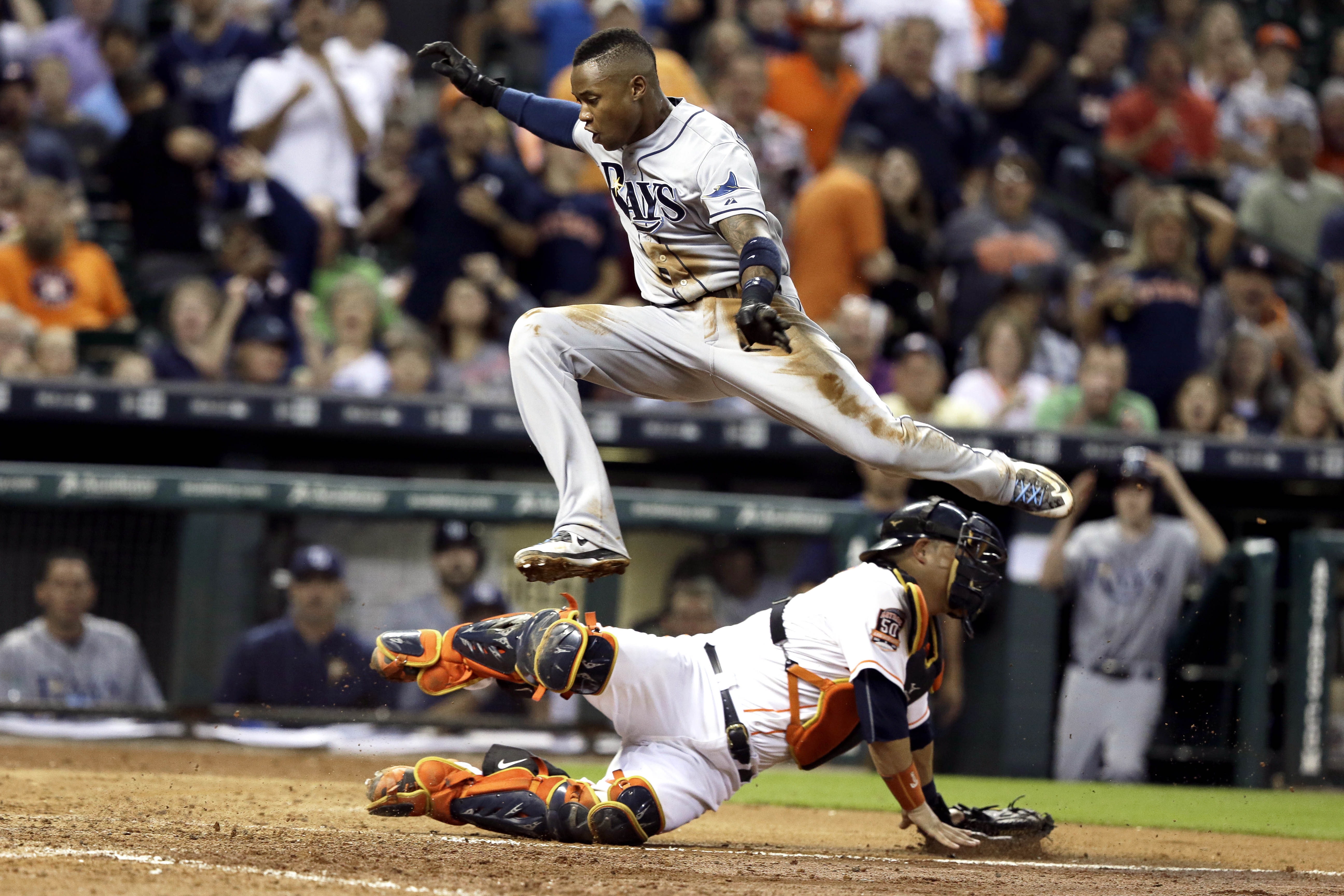 Tampa Bay Rays' Tim Beckham leaps over Houston Astros catcher Hank Conger to score on a James Loney sacrifice fly during the seventh inning of a baseball game Wednesday, Aug. 19, 2015, in Houston. (AP Photo/Pat Sullivan)