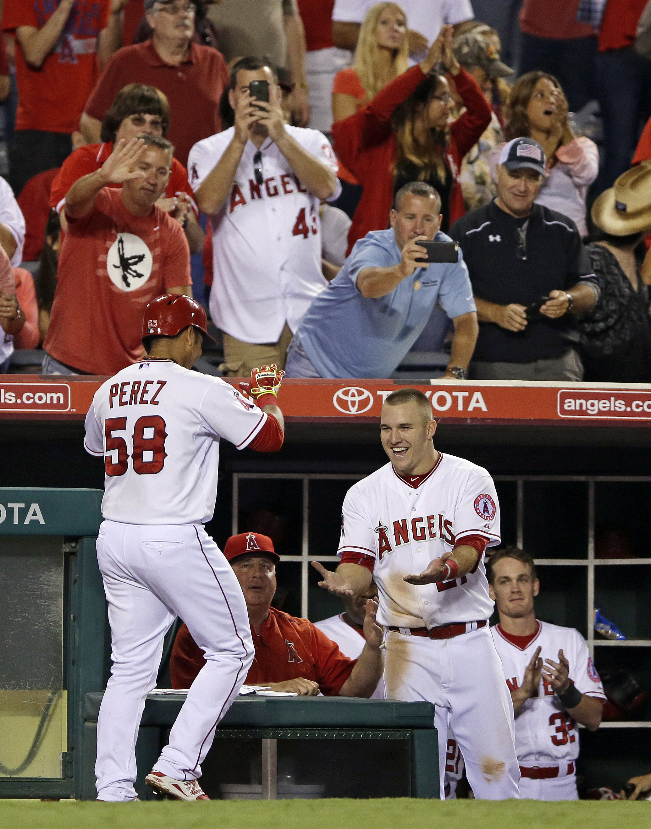 Los Angeles Angels' Carlos Perez, left, celebrates with Mike Trout after hitting a home run against the Chicago White Sox during the sixth inning of a baseball game in Anaheim, Calif., Wednesday, Aug. 19, 2015. (AP Photo/Chris Carlson)