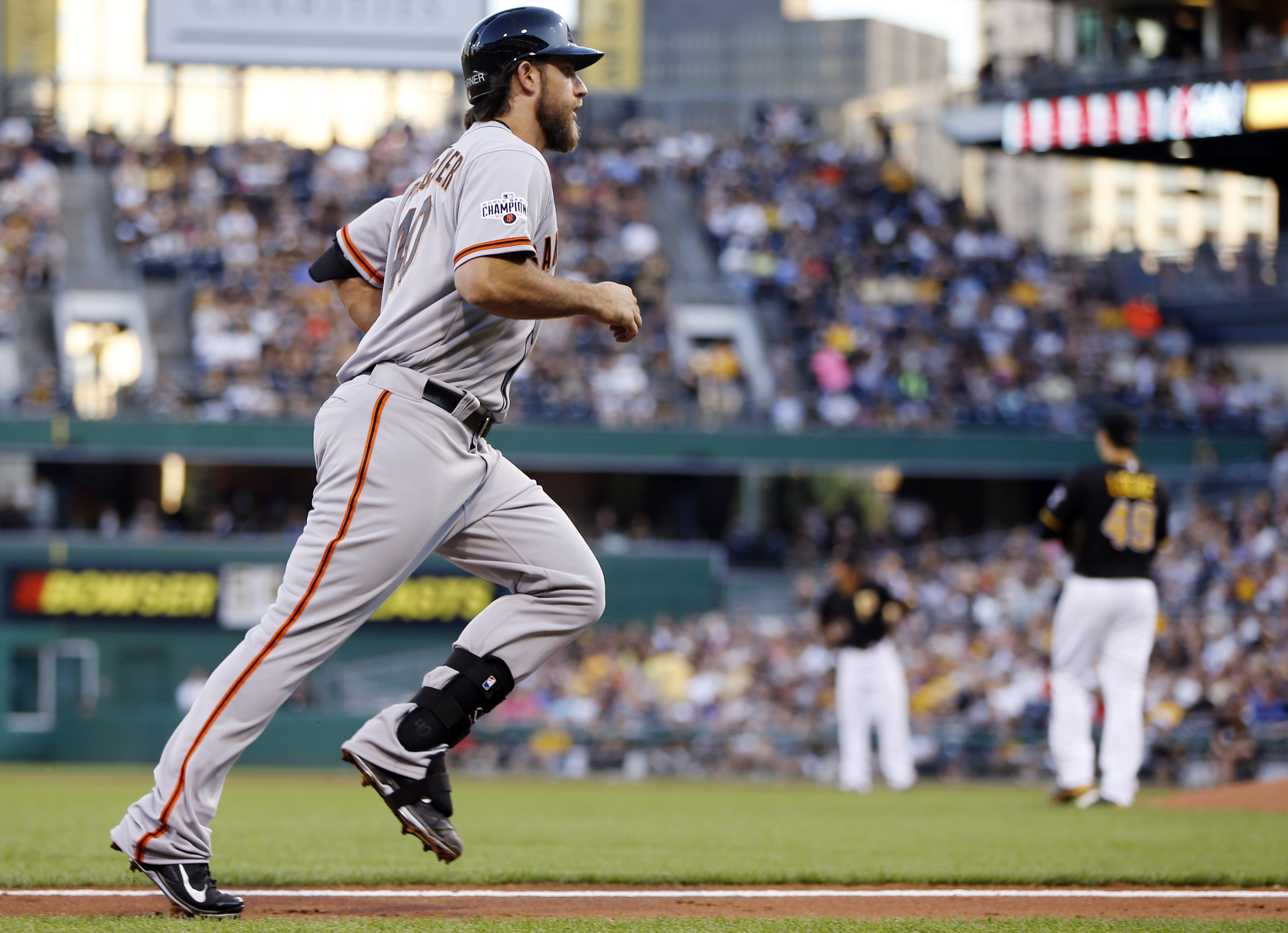 San Francisco Giants starting pitcher Madison Bumgarner, left, rounds the bases after hitting a two-run home run off Pittsburgh Pirates starting pitcher Jeff Locke, right, in the second inning of a baseball game, Friday, Aug. 21, 2015, in Pittsburgh. (AP