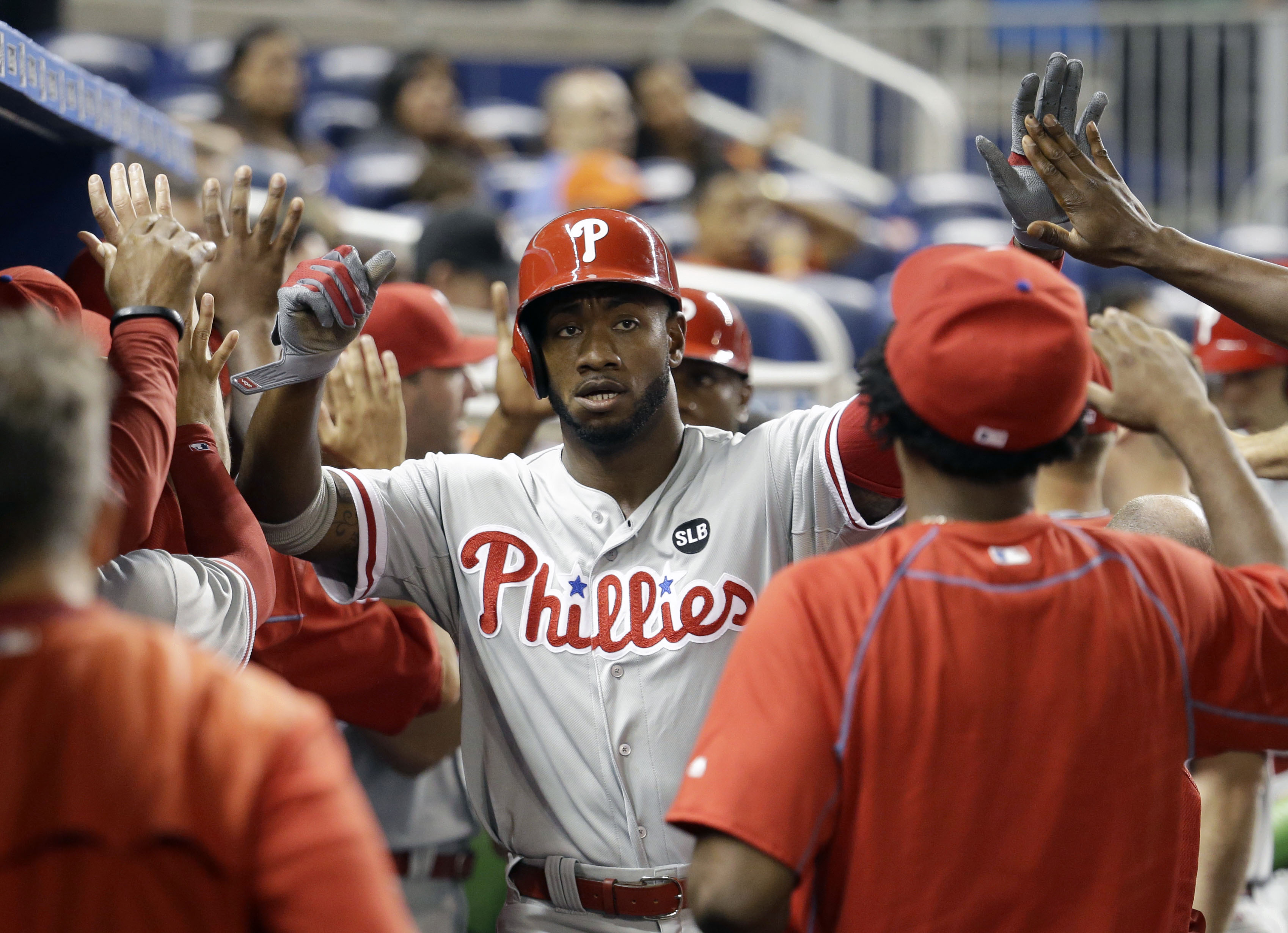 Philadelphia Phillies' Domonic Brown is congratulated in the dugout after scoring on a single hit by Jerad Eickhoff in the fourth inning  of a baseball game against the Miami Marlins, Friday, Aug. 21, 2015, in Miami. (AP Photo/Lynne Sladky)