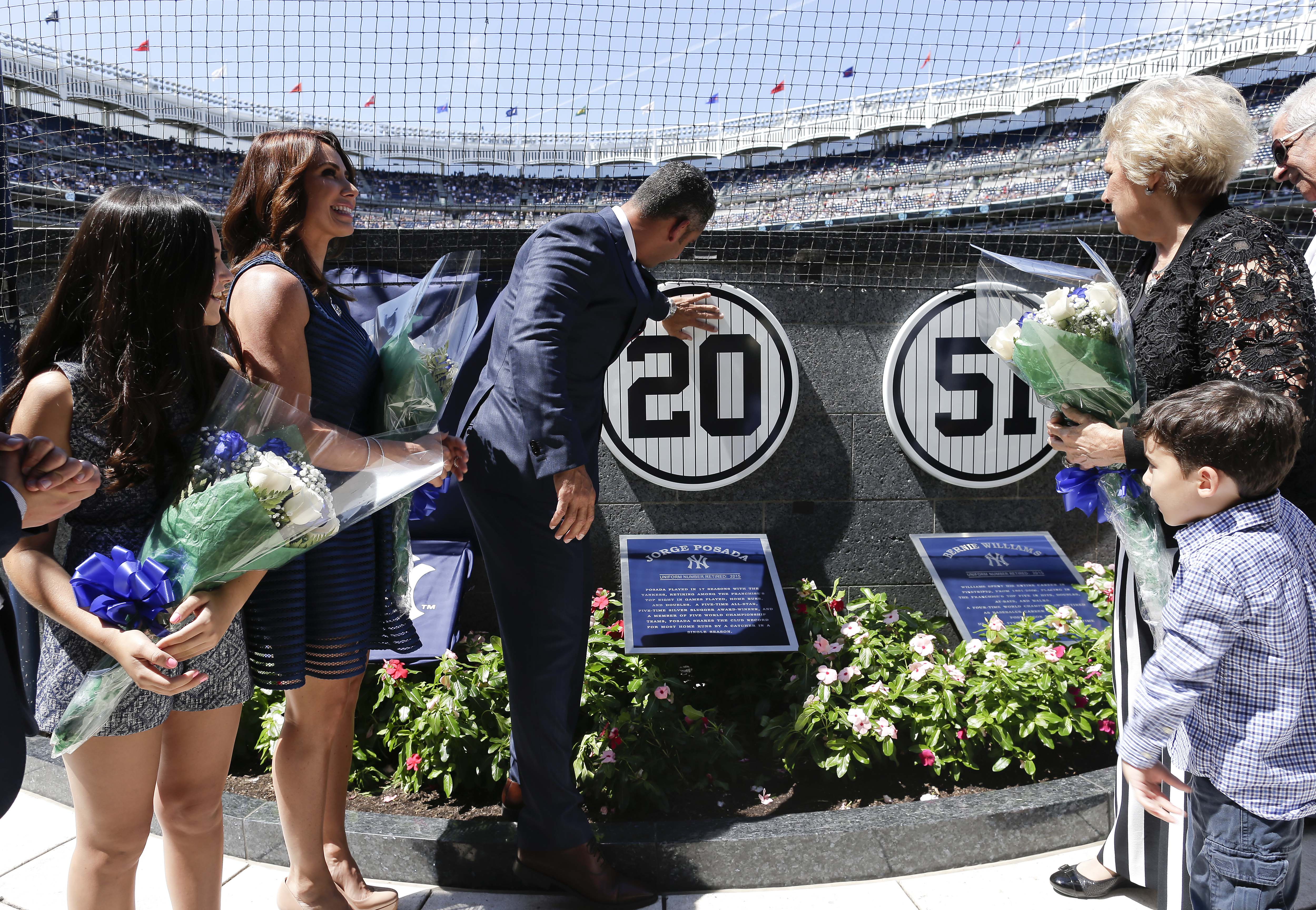 Accompanied by family members, former New York Yankees catcher Jorge Posada touches a plague with his jersey number on a wall in Monument Park during a ceremony retiring his number before a baseball game against the Cleveland Indians, Saturday, Aug. 22, 2