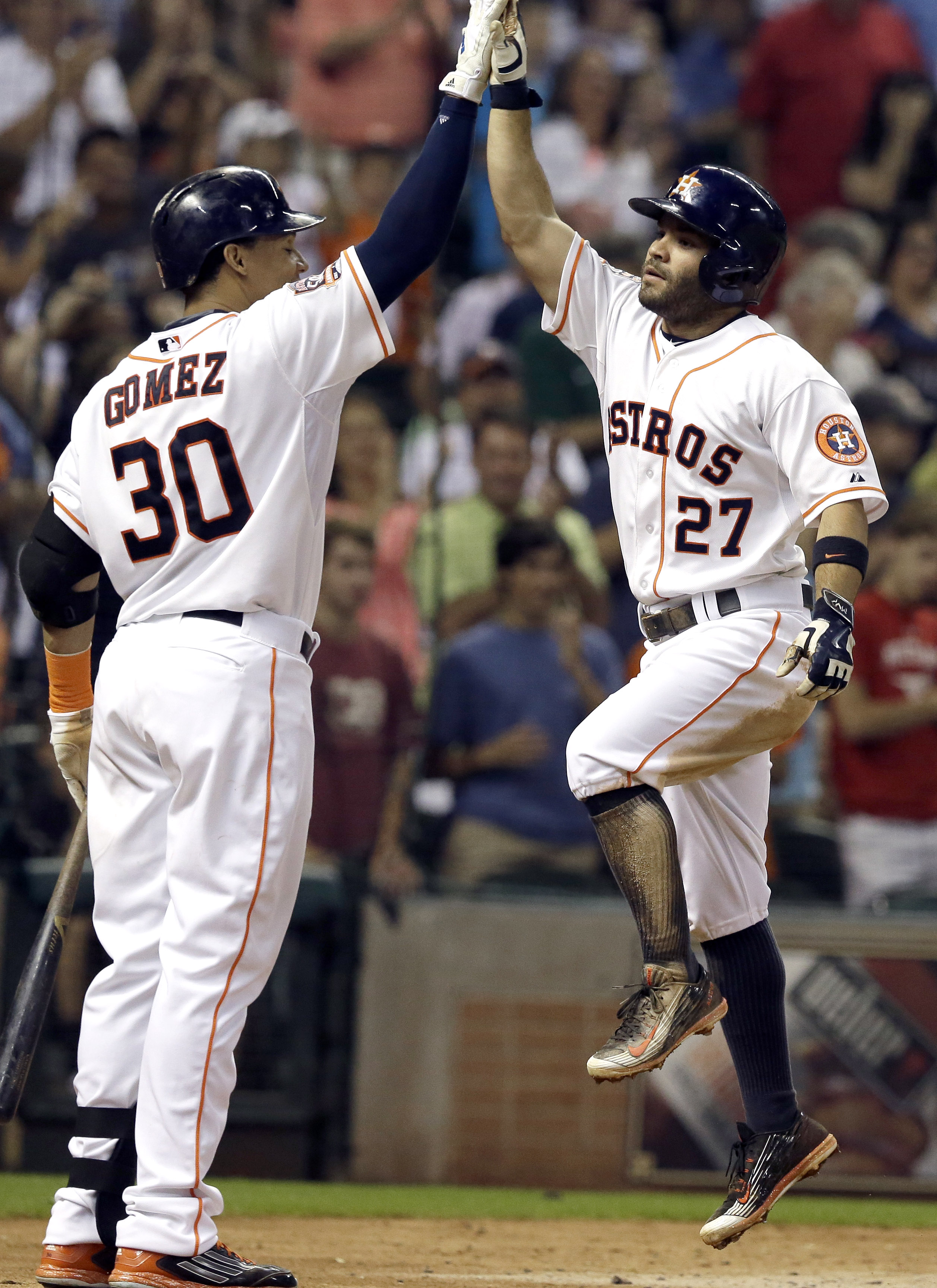 Houston Astros' Carlos Gomez (30) high-fives Jose Altuve (27) after Altuve's solo home run against the Los Angeles Dodgers during the sixth inning of a baseball game Saturday, Aug. 22, 2015, in Houston. (AP Photo/Pat Sullivan)