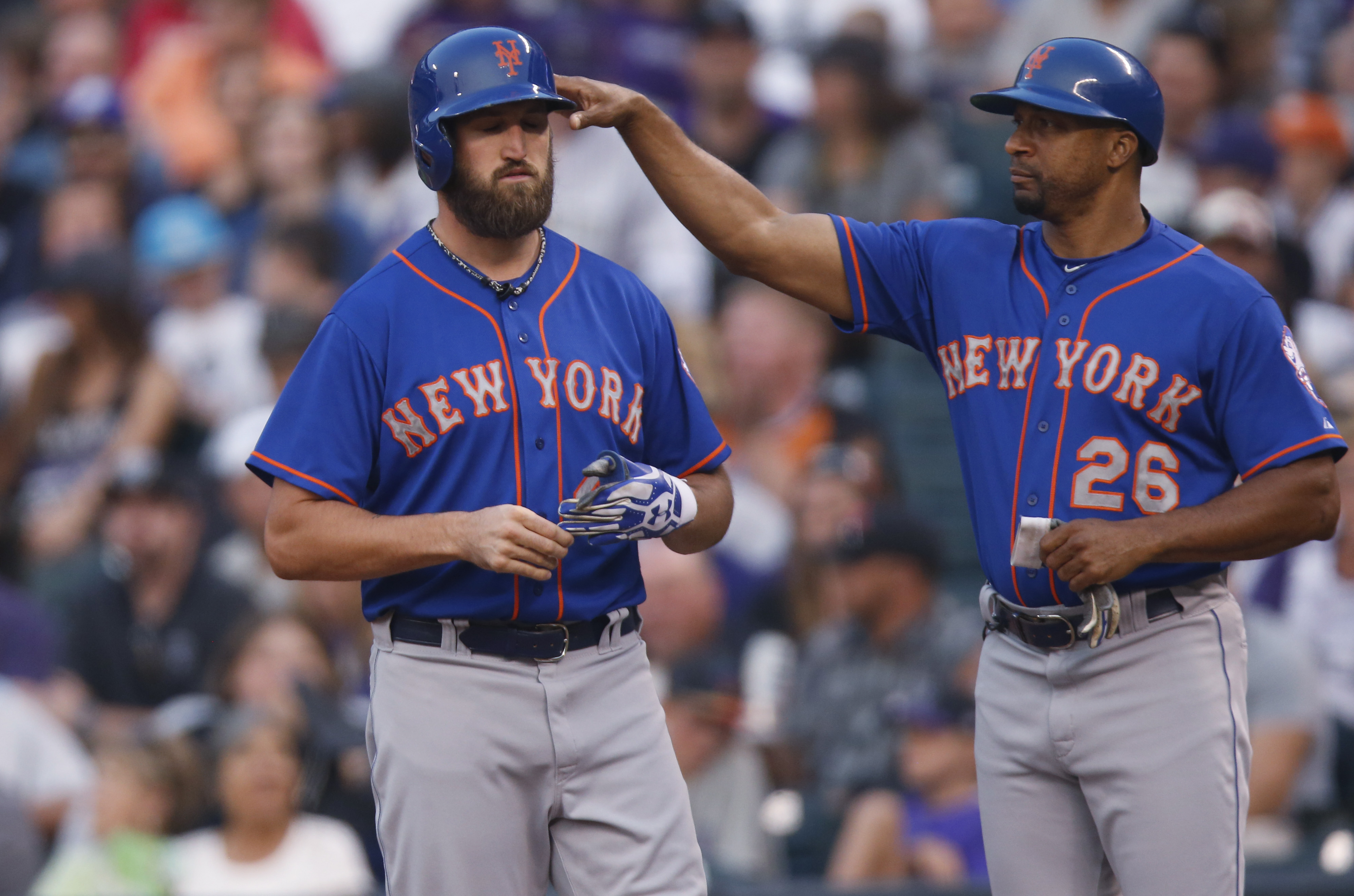 New York Mets' Jonathon Niese, left, is tapped on the helmet by first base coach Tom Goodwin after hitting a single with the bases loaded to drive in two runs off Colorado Rockies starting pitcher Chris Rusin in the third inning of a baseball game Saturda
