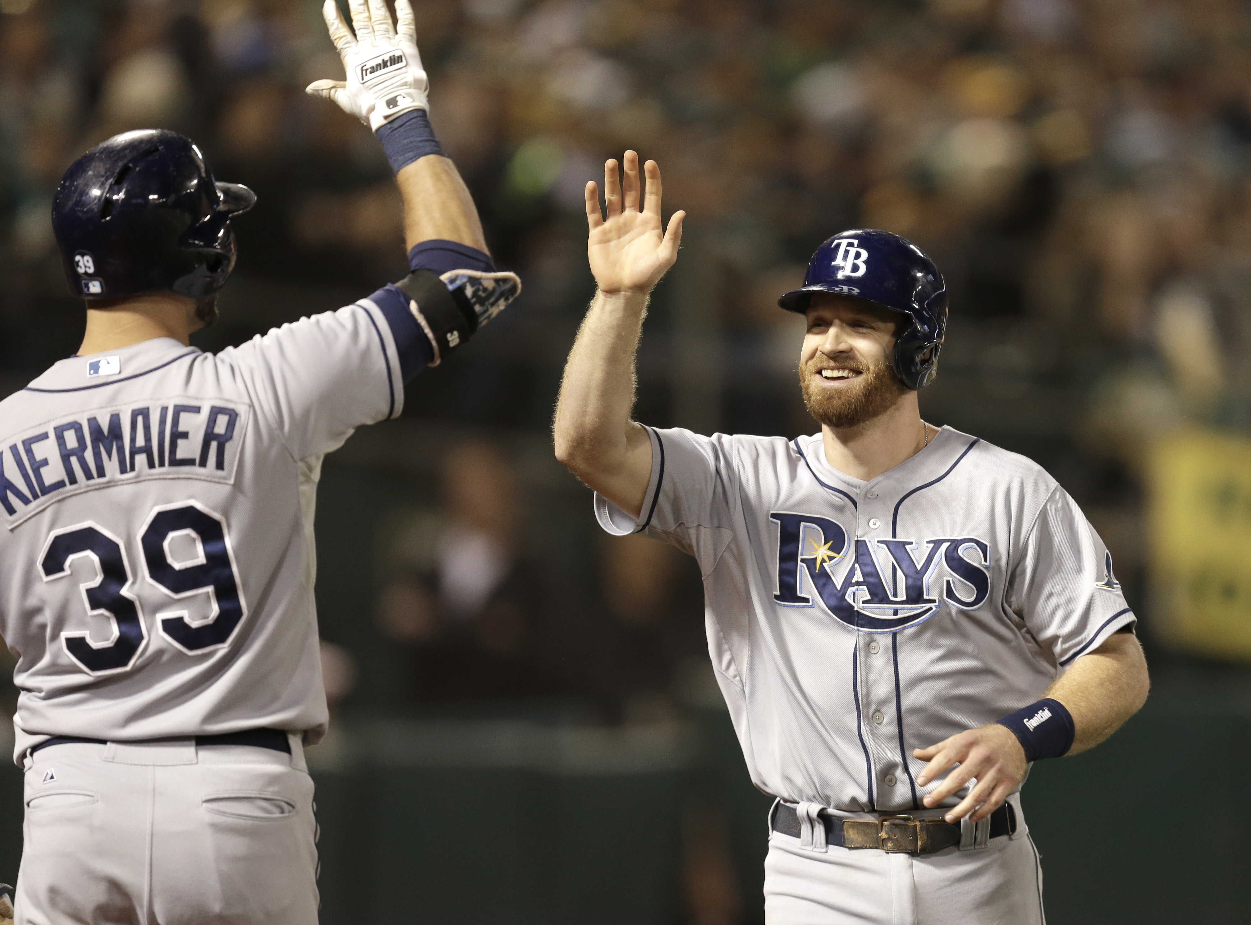Tampa Bay Rays' Logan Forsythe, right, is congratulated by Kevin Kiermaier (39) after scoring against the Oakland Athletics in the ninth inning of a baseball game Saturday, Aug. 22, 2015, in Oakland, Calif. Forsythe scored on a double by Rays' Asdrubal Ca