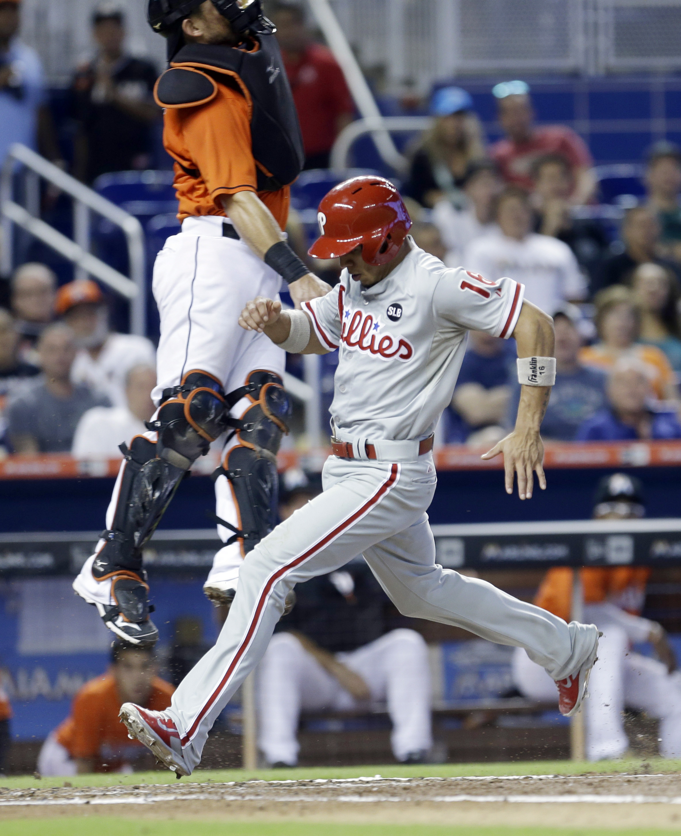 Philadelphia Phillies' Cesar Hernandez (16) scores on a sacrifice fly by Aaron Altherr as Miami Marlins catcher Jeff Mathis, left, leaps for the ball in the third inning of a baseball game, Sunday, Aug. 23, 2015, in Miami. (AP Photo/Alan Diaz)