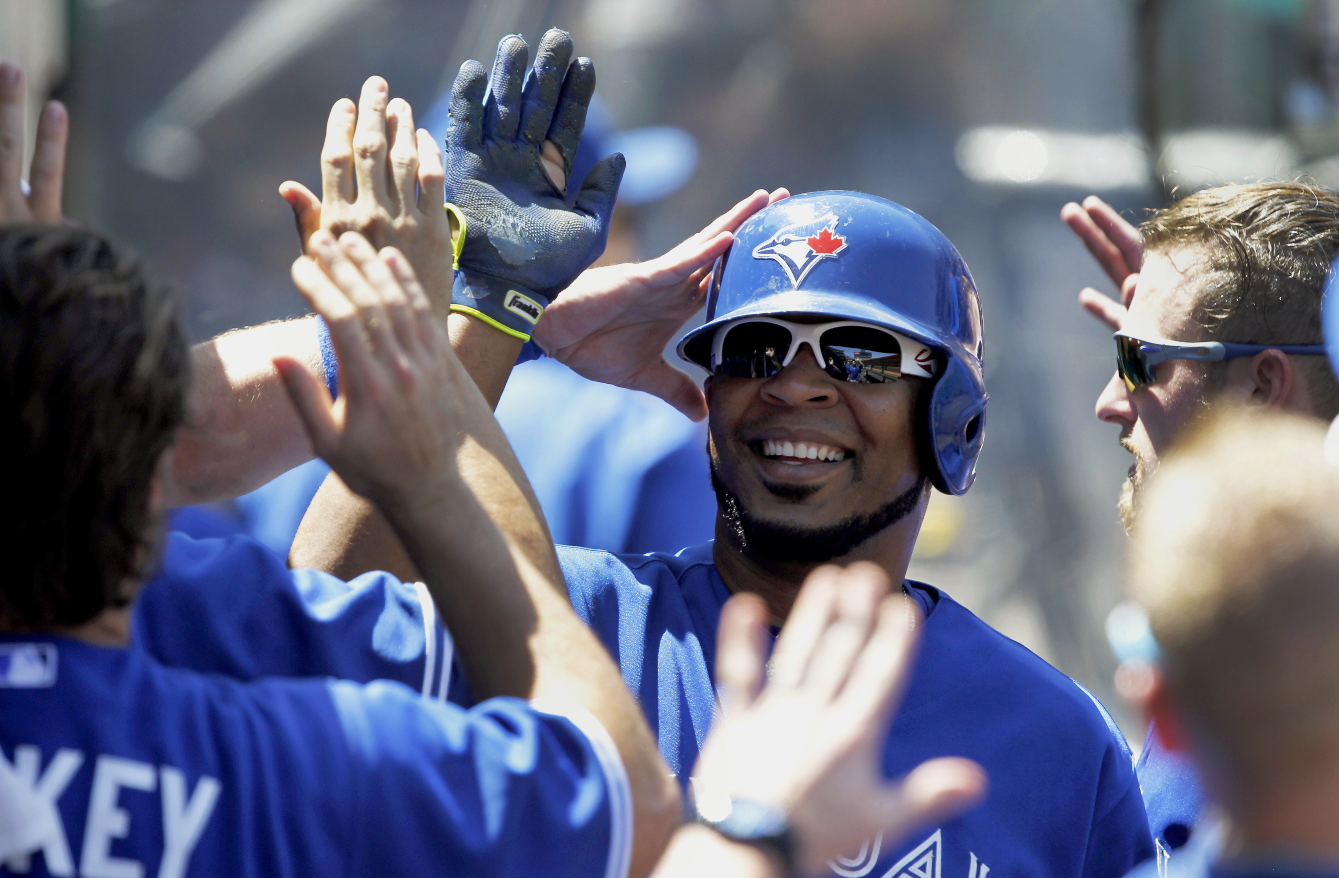 Toronto Blue Jays' Edwin Encarnacion, center, gets congratulations from teammates after scoring on an infield single by Ben Revere during the third inning of a baseball game against the Los Angeles Angels in Anaheim, Calif., Sunday, Aug. 23, 2015. (AP Pho