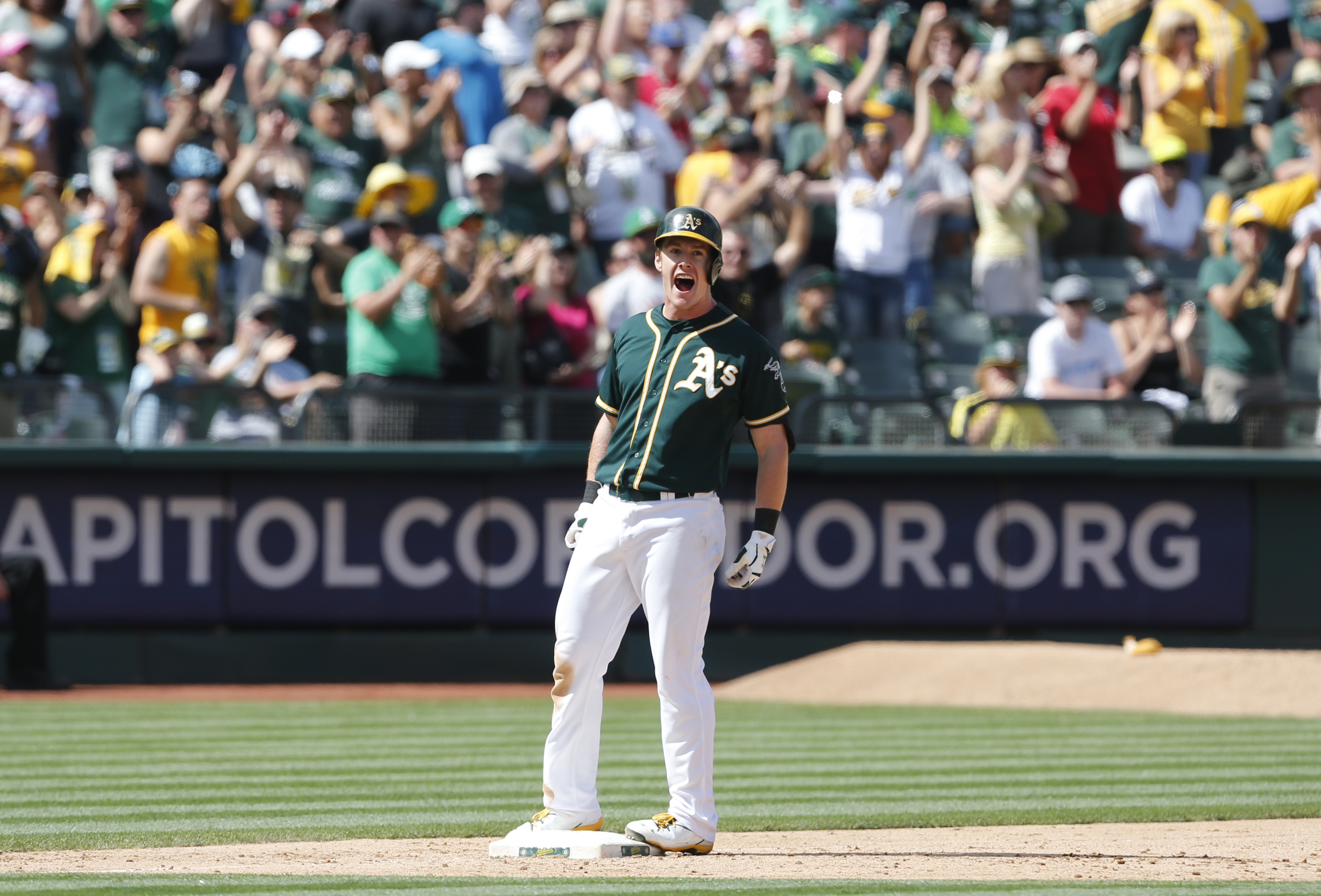 Oakland Athletics' Mark Cahn celebrates after hitting a 3 RBI triple during the seventh inning of a baseball game against the Tampa Bay Rays, Sunday, Aug. 23, 2015, in Oakland, Calif. (AP Photo/Beck Diefenbach)