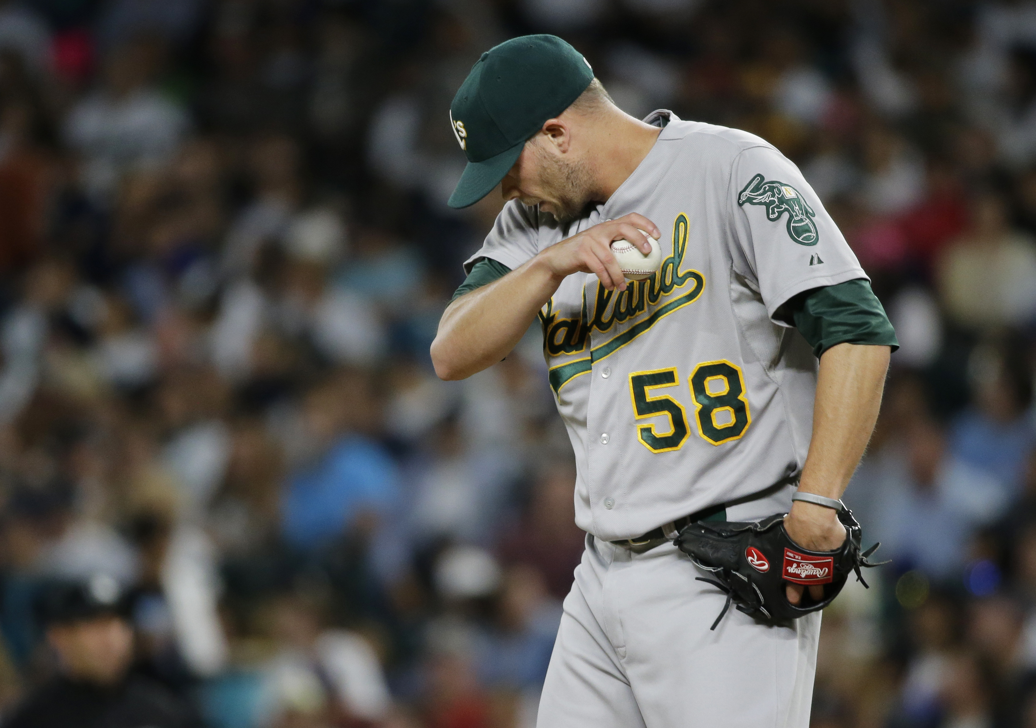 Oakland Athletics pitcher Evan Scribner wipes his forehead after giving up a three-run home run to Seattle Mariners' Franklin Gutierrez in the third inning of a baseball game, Monday, Aug. 24, 2015, in Seattle. (AP Photo/Ted S. Warren)
