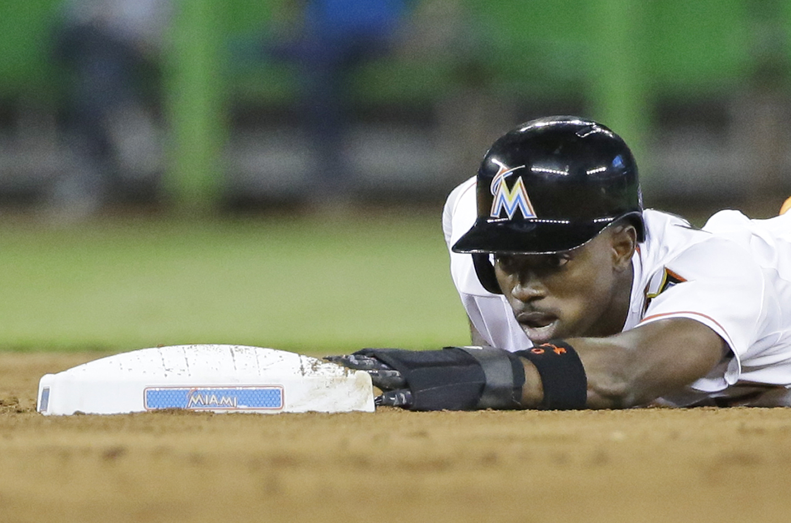 Miami Marlins' Dee Gordon hangs on to the base after stealing second during the fourth inning of a baseball game against the Pittsburgh Pirates, Tuesday, Aug. 25, 2015, in Miami. (AP Photo/Wilfredo Lee)