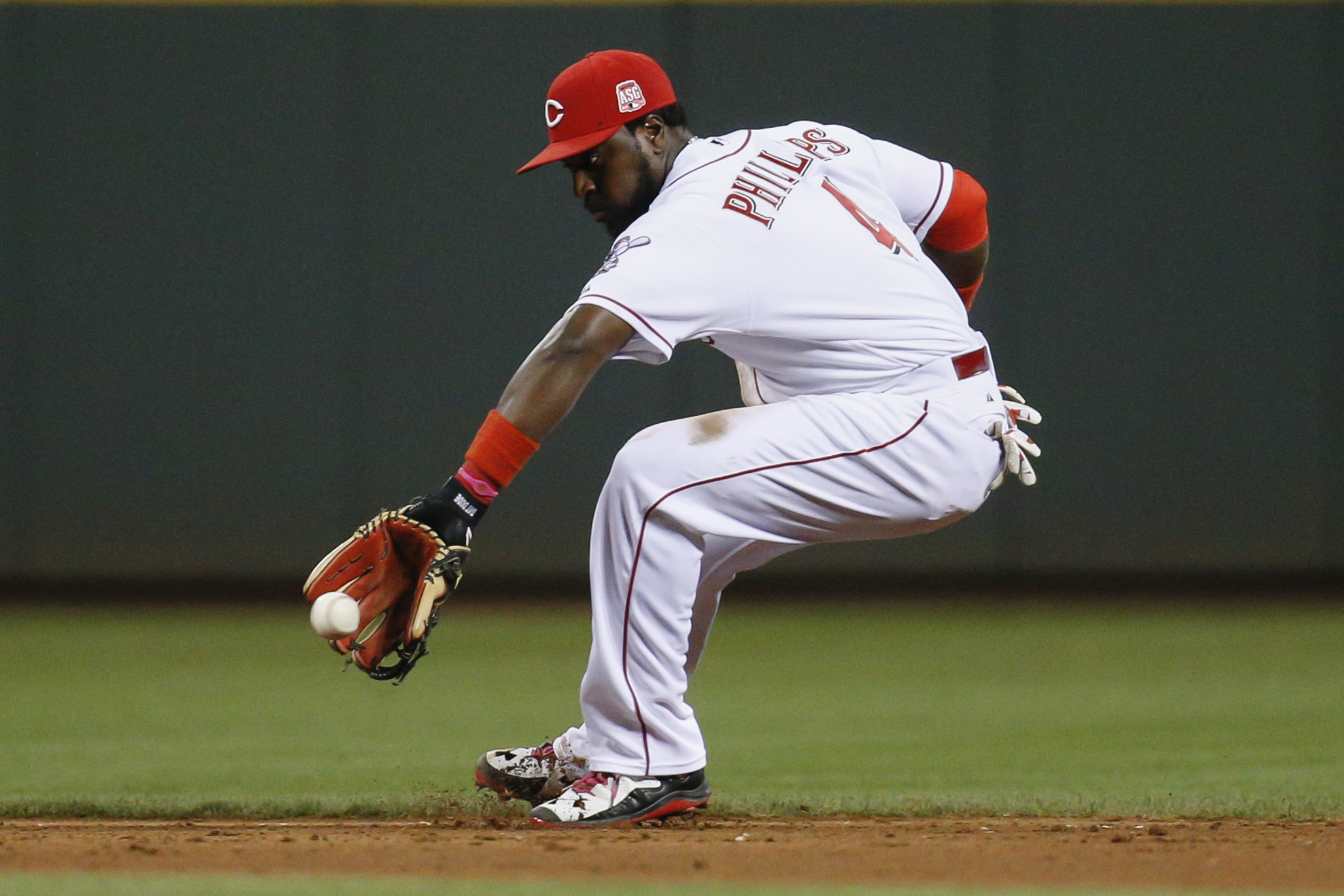 Cincinnati Reds second baseman Brandon Phillips fields a ground ball from Los Angeles Dodgers' Chase Utley during the eighth inning of a baseball game, Tuesday, Aug. 25, 2015, in Cincinnati. Phillips threw out Utley at first base. (AP Photo/John Minchillo