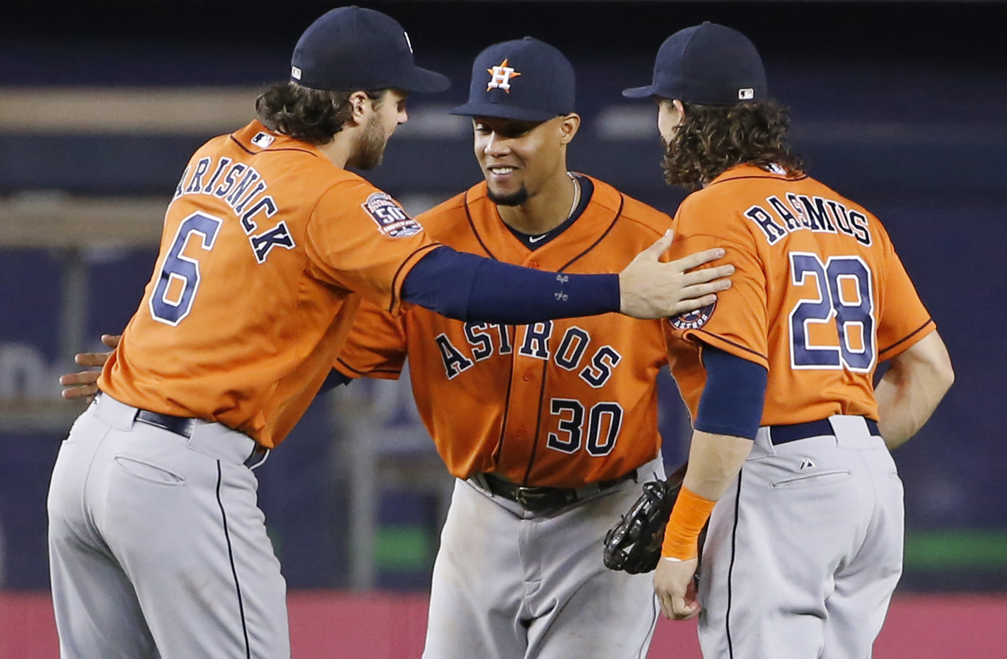 Houston Astros left fielder Jake Marisnick (6) congratulates center fielder Carlos Gomez (30) right fielder Colby Rasmus (28) after the Astros' 15-1 victory over the New York Yankees in a baseball game at Yankee Stadium in New York, Tuesday, Aug. 25, 2015