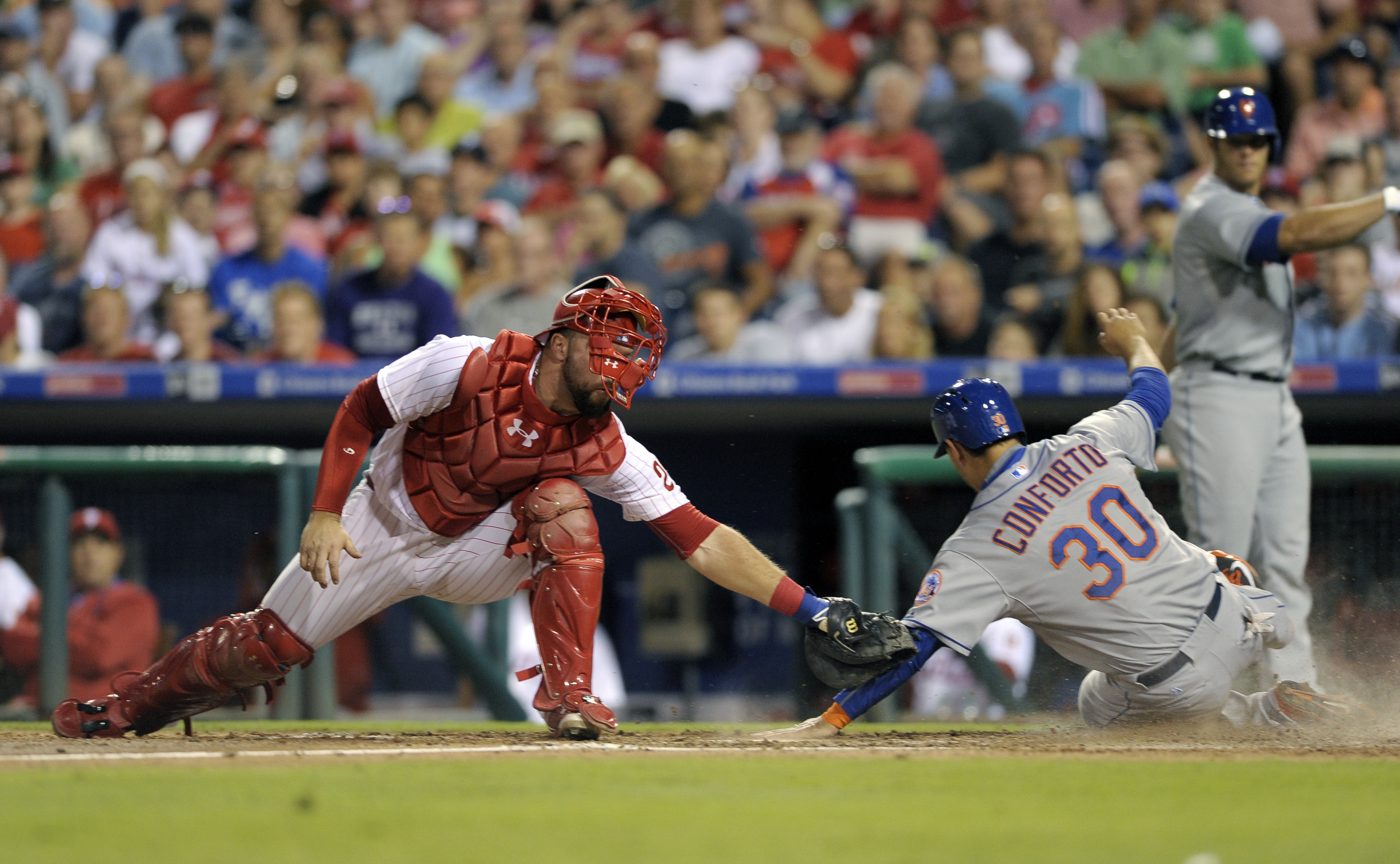 New York Mets' Michael Conforto (30) slides past Philadelphia Phillies catcher Cameron Rupp, left, and score on a Juan Uribe single in the sixth inning of a baseball game, Wednesday, Aug. 26, 2015, in Philadelphia. (AP Photo/Michael Perez)