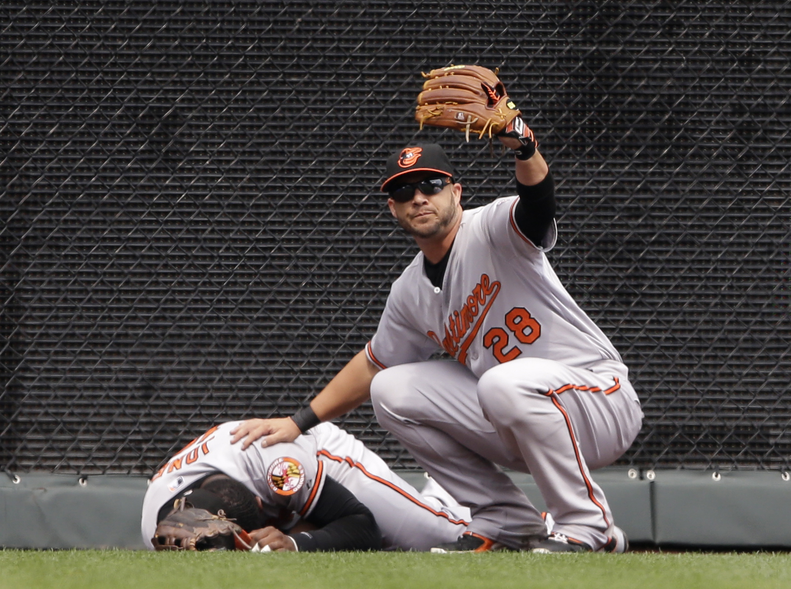 Baltimore Orioles left fielder Steve Pearce (28) calls for help after center fielder Adam Jones, left, hit the wall while chasing a fly ball during the first inning of a baseball game against the Kansas City Royals at Kauffman Stadium in Kansas City, Mo.,