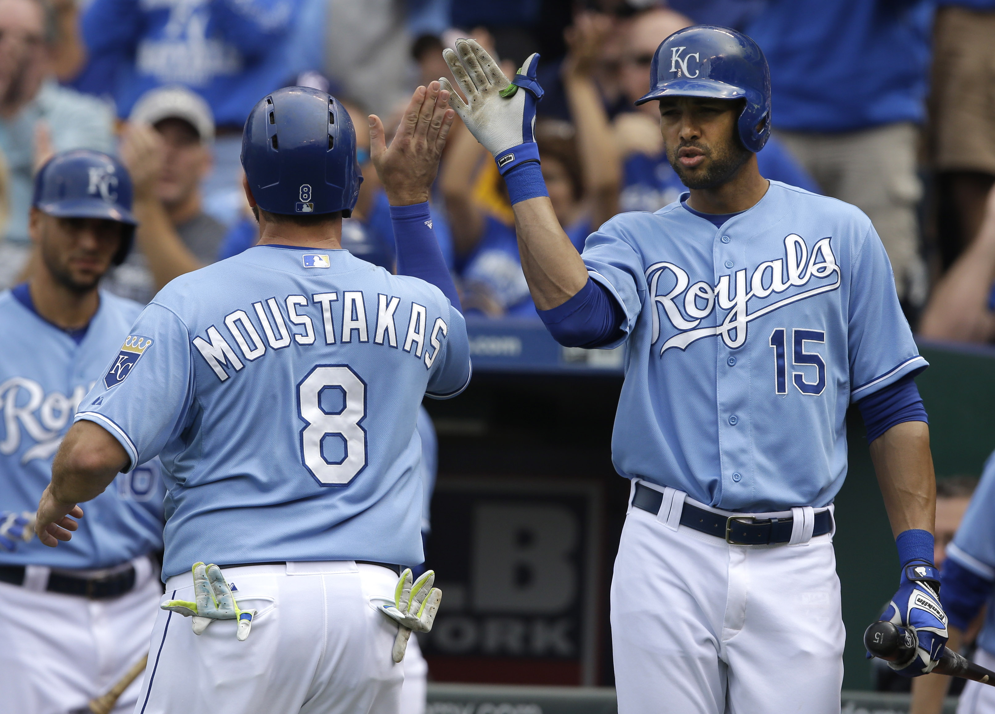 Kansas City Royals' Mike Moustakas (8) is congratulated by on-deck batter Alex Rios (15) after scoring on a single by teammate Salvador Perez during the fourth inning of a baseball game against the Baltimore Orioles at Kauffman Stadium in Kansas City, Mo.