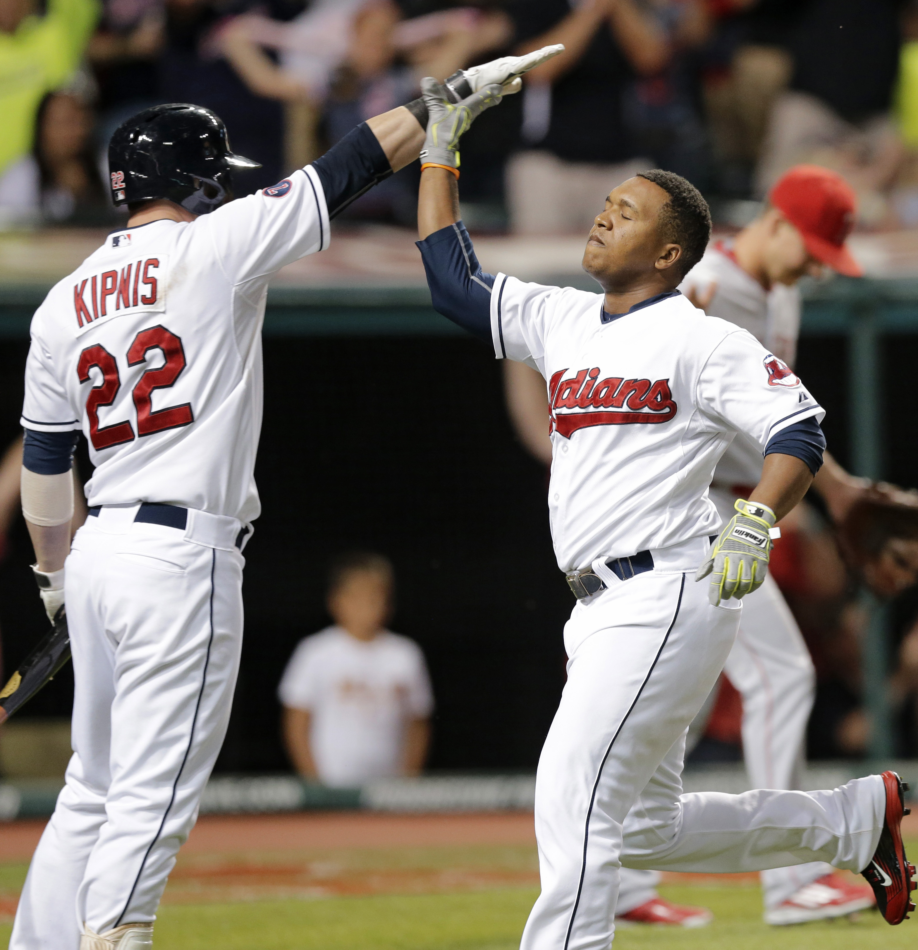 Cleveland Indians' Jose Ramirez, right, is congratulated by Jason Kipnis after Ramirez scored on a double by Abraham Almonte during the seventh inning of a baseball game against the Los Angeles Angels, Friday, Aug. 28, 2015, in Cleveland. (AP Photo/Tony D