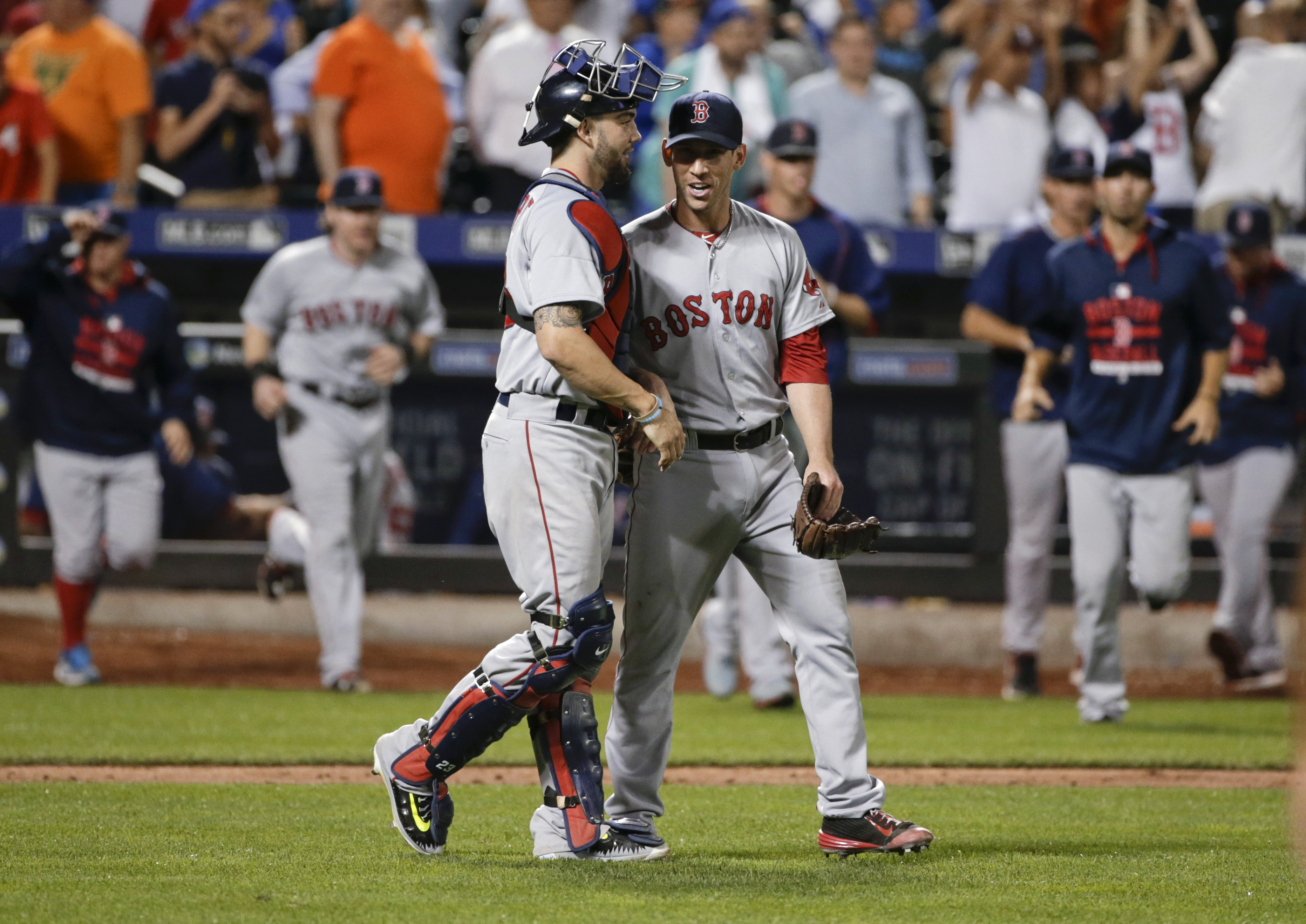 Boston Red Sox relief pitcher Jean Machi, right, and catcher Blake Swihart meet after the Red Sox defeated the New York Mets 6-4 in a baseball game Friday, Aug. 28, 2015, in New York. (AP Photo/Frank Franklin II)