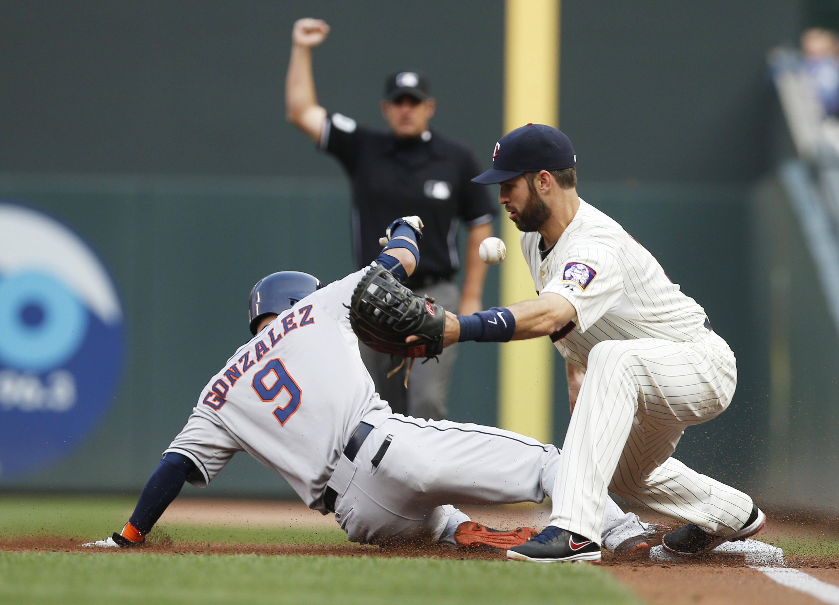 First base umpire Mark Ripperger makes an early out call on a double play attempt but Houston Astros' Marwin Gonzalez winds up safely at first when Minnesota Twins first baseman Joe Mauer can't handle the throw after Marvin Gonale flew out to center in th