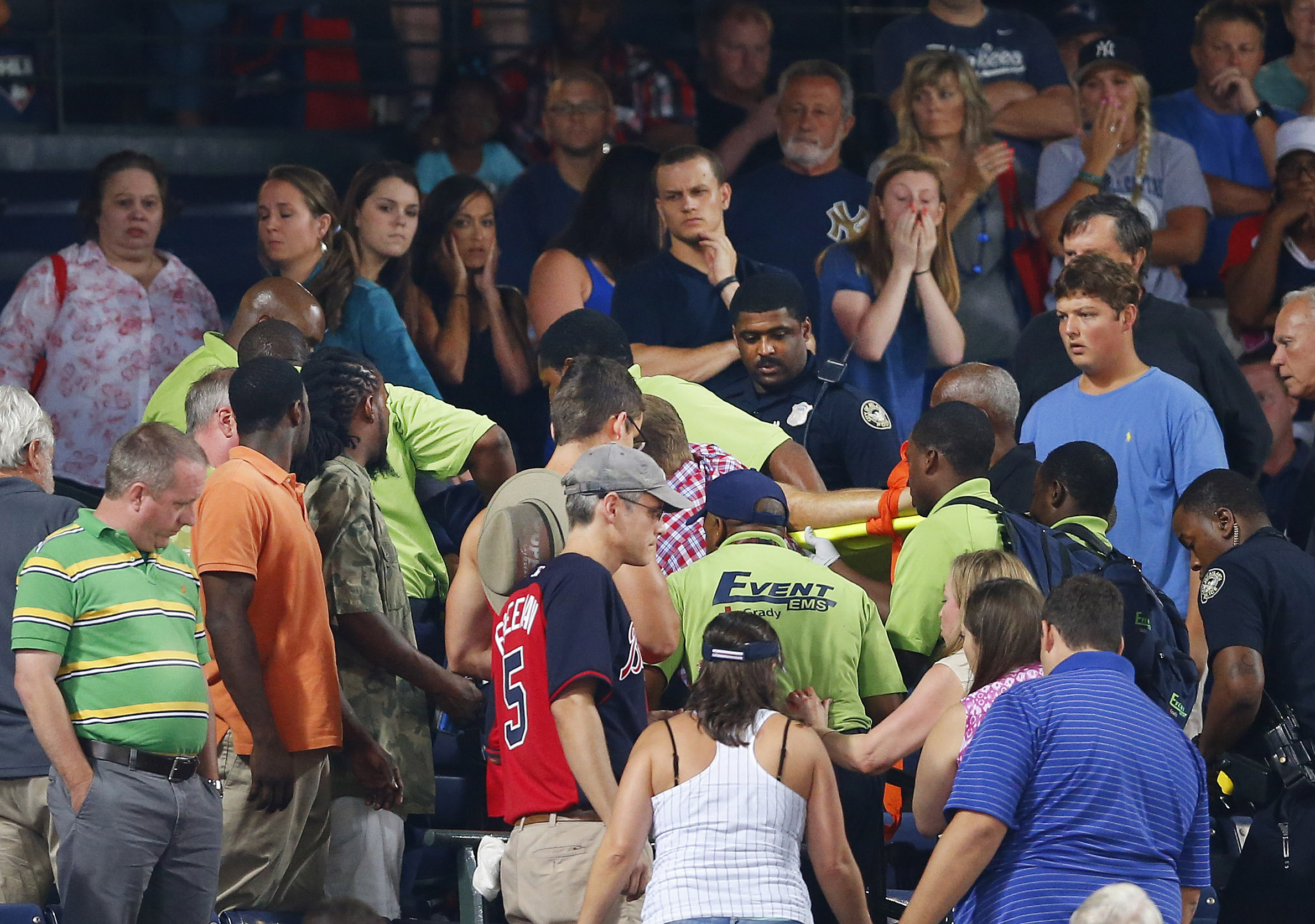 Rescue workers carry an injured fan from the stands at Turner Field during a baseball game between Atlanta Braves and New York Yankees Saturday, Aug. 29, 2015, in Atlanta. A fan has been given emergency medical treatment and been taken to a hospital after